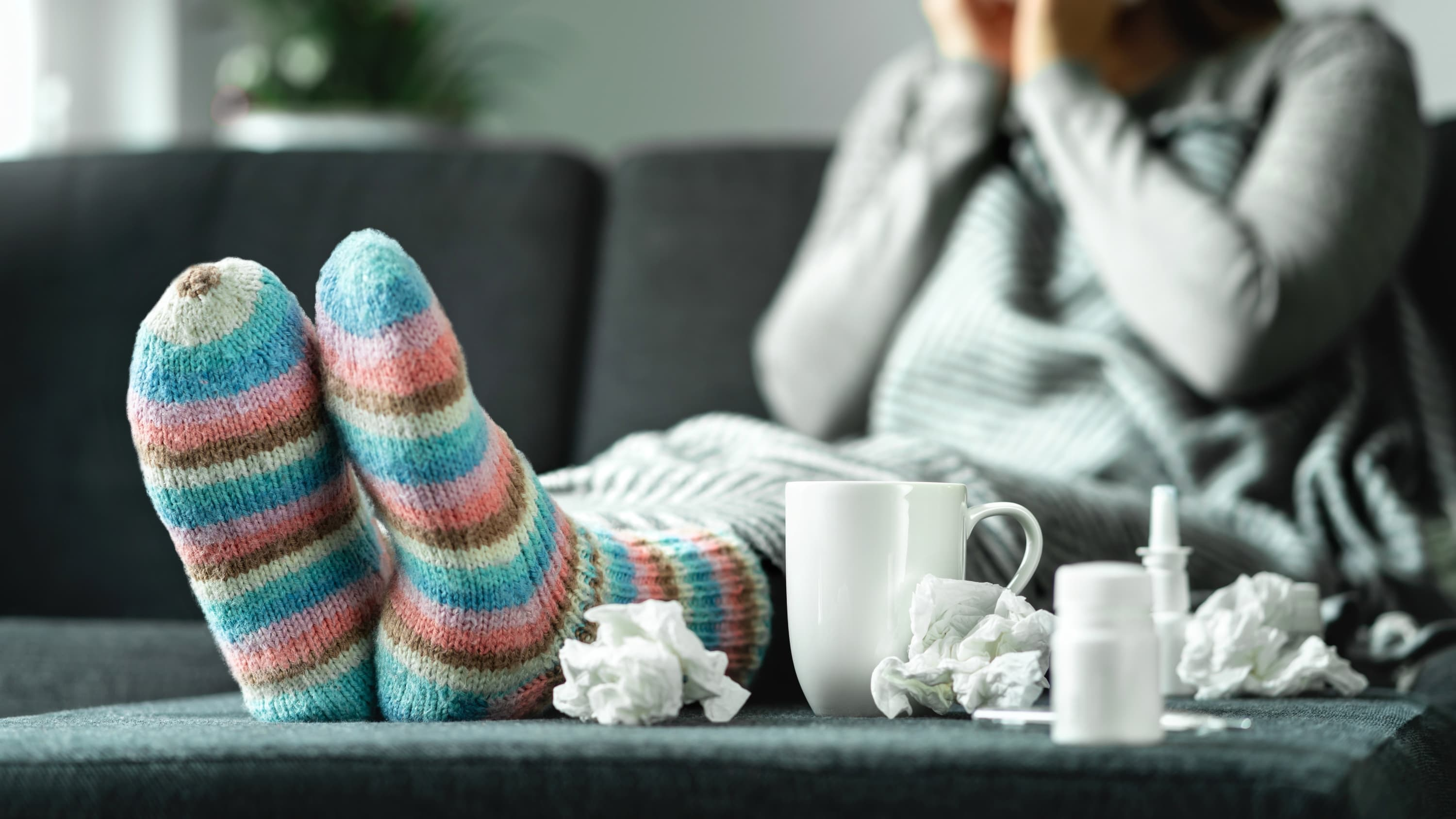person on the couch sick with cold, flu, or covid-19