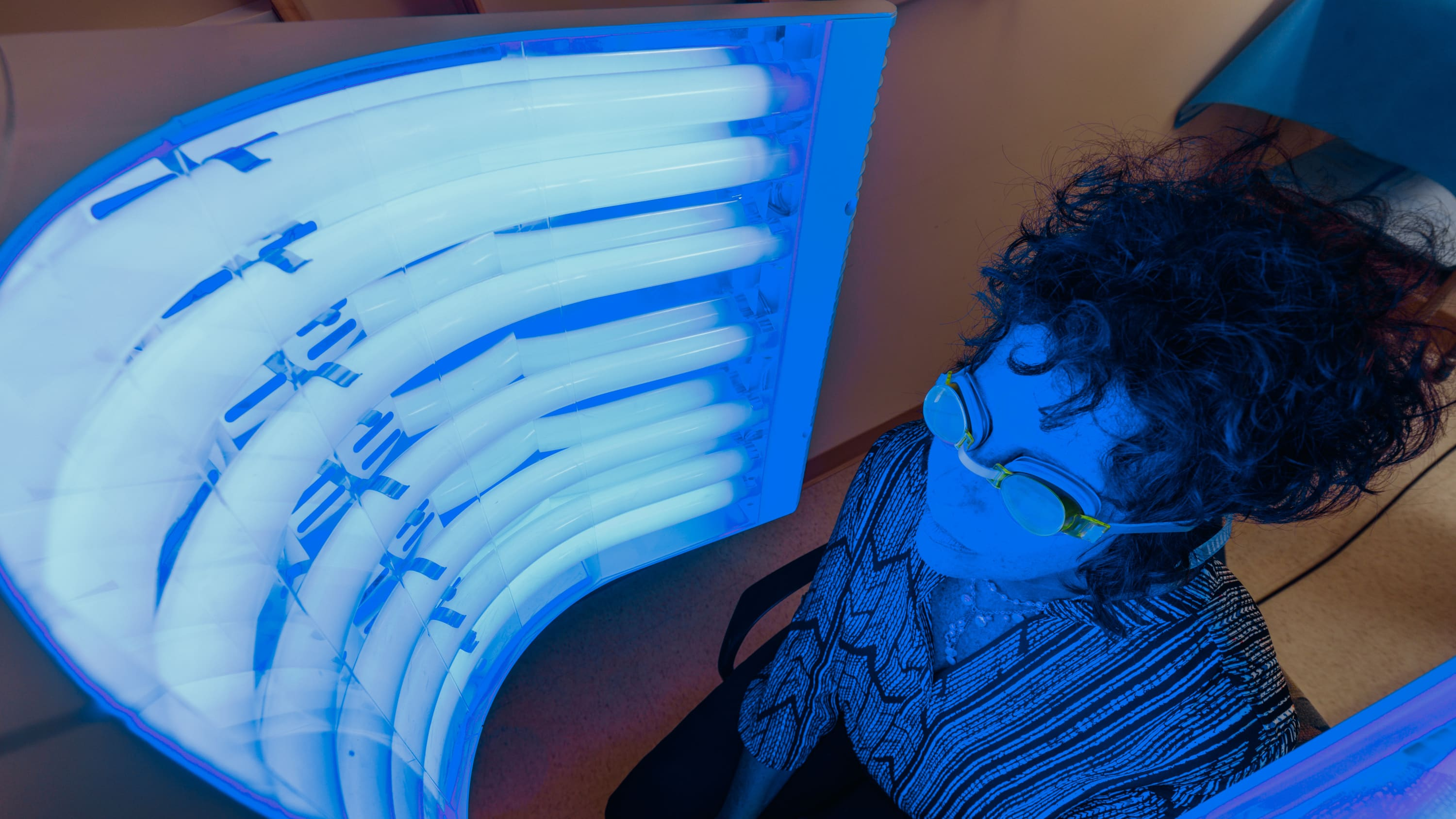 A woman sits in front of a device as she receives photodynamic therapy