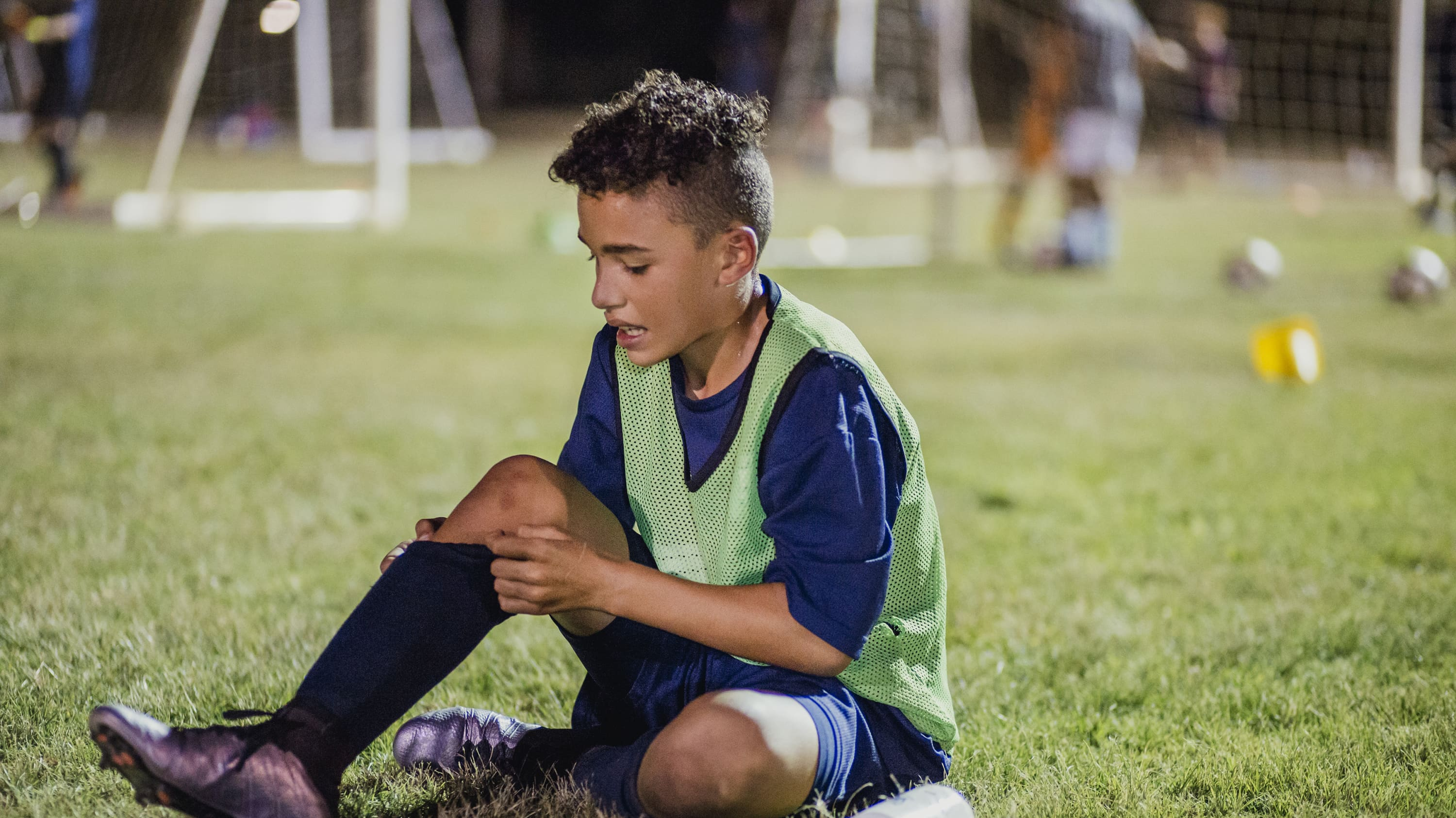 A boy injures himself, with possibly a growth plate injury, playing soccer.