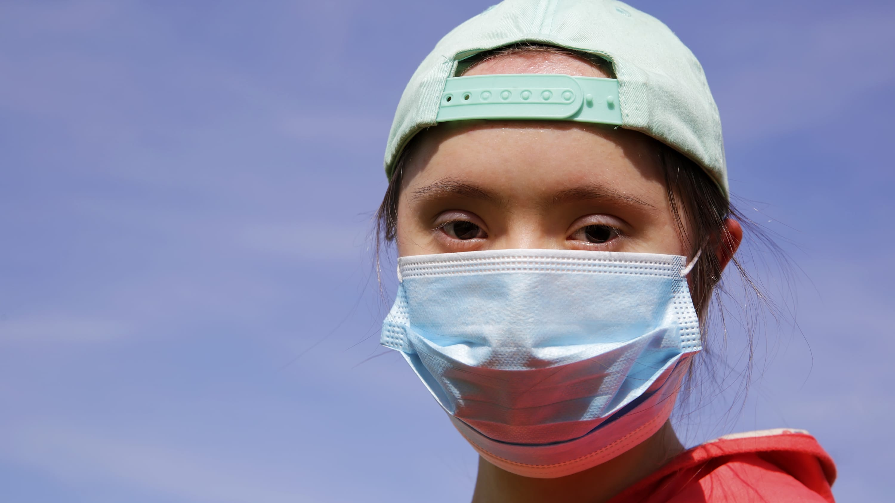 young girl with Down syndrome wearing a mask to protect against COVID-19