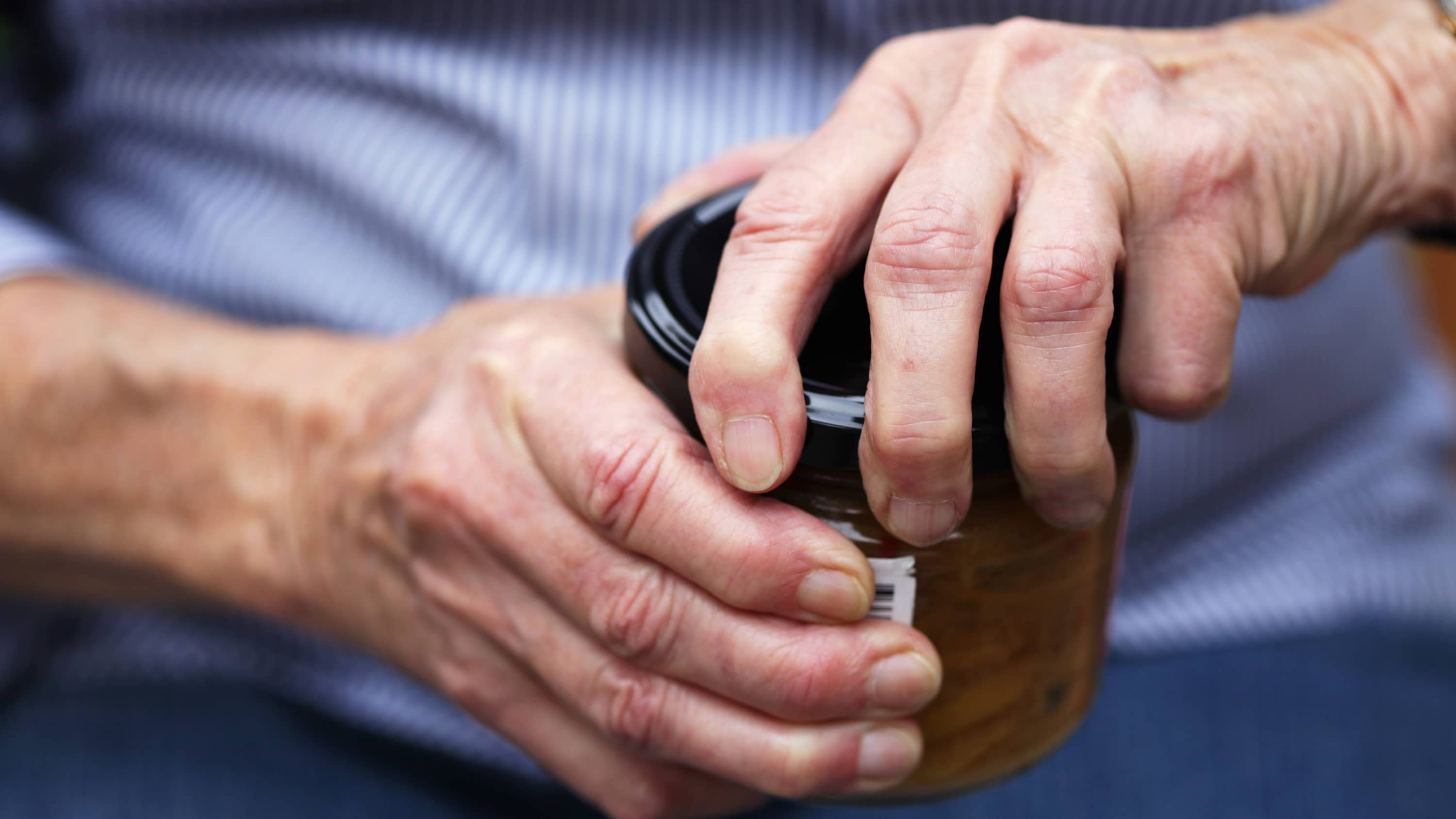 Older person with arthritis having difficulty opening a jar