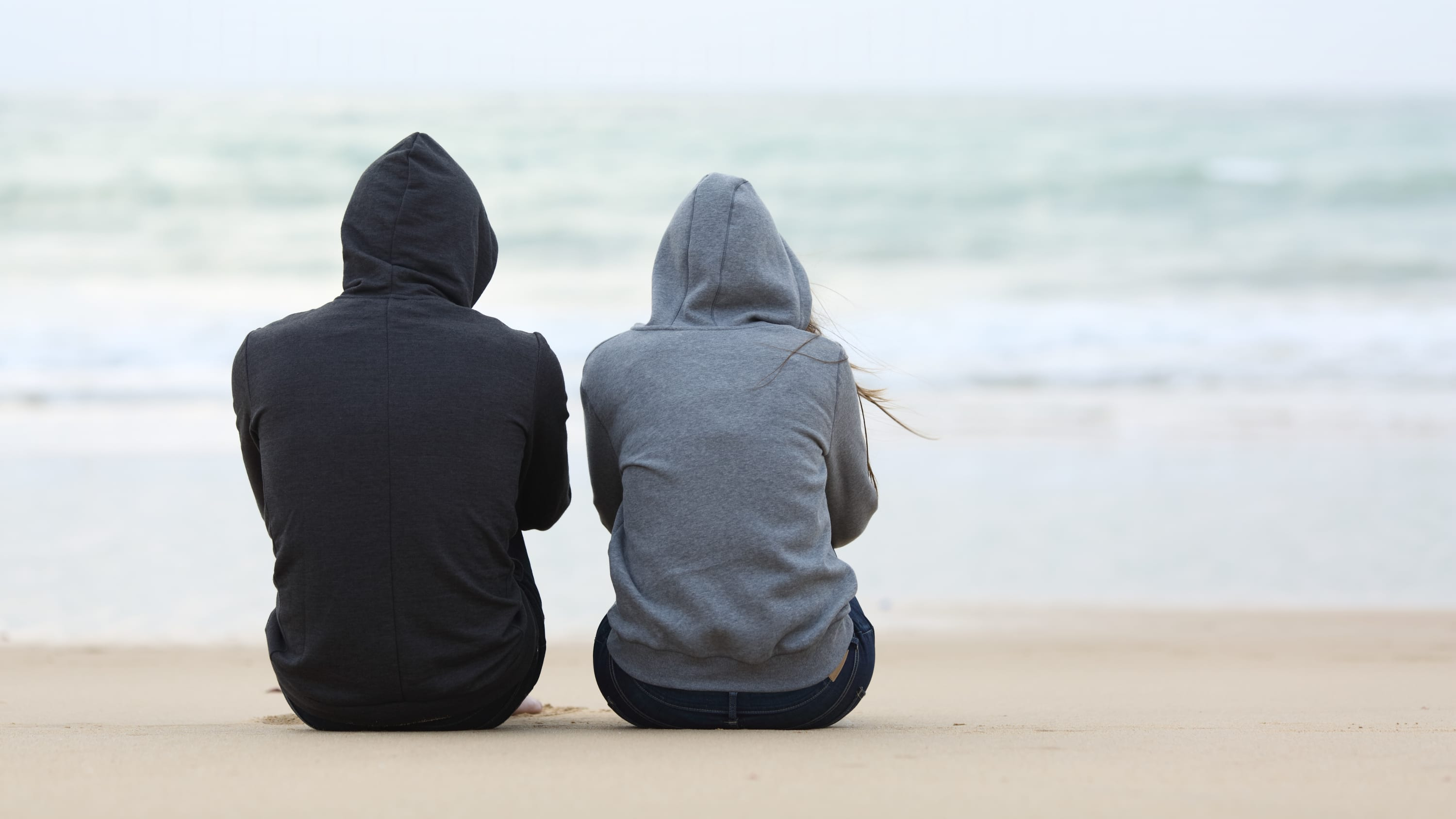 A man and a woman sit on a beach, possibly talking about herpes