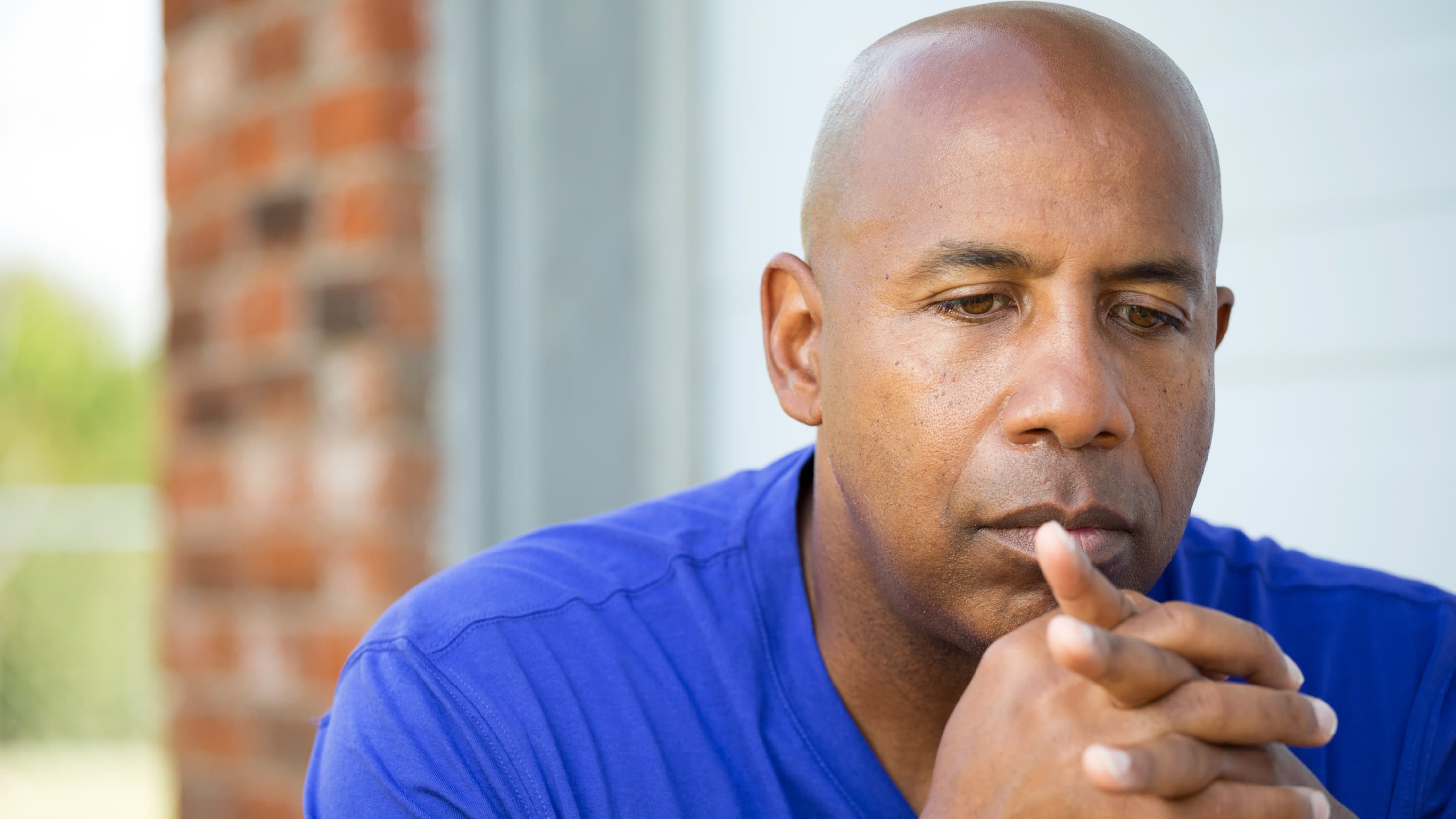 A man who may have a hernia sits with a worried look