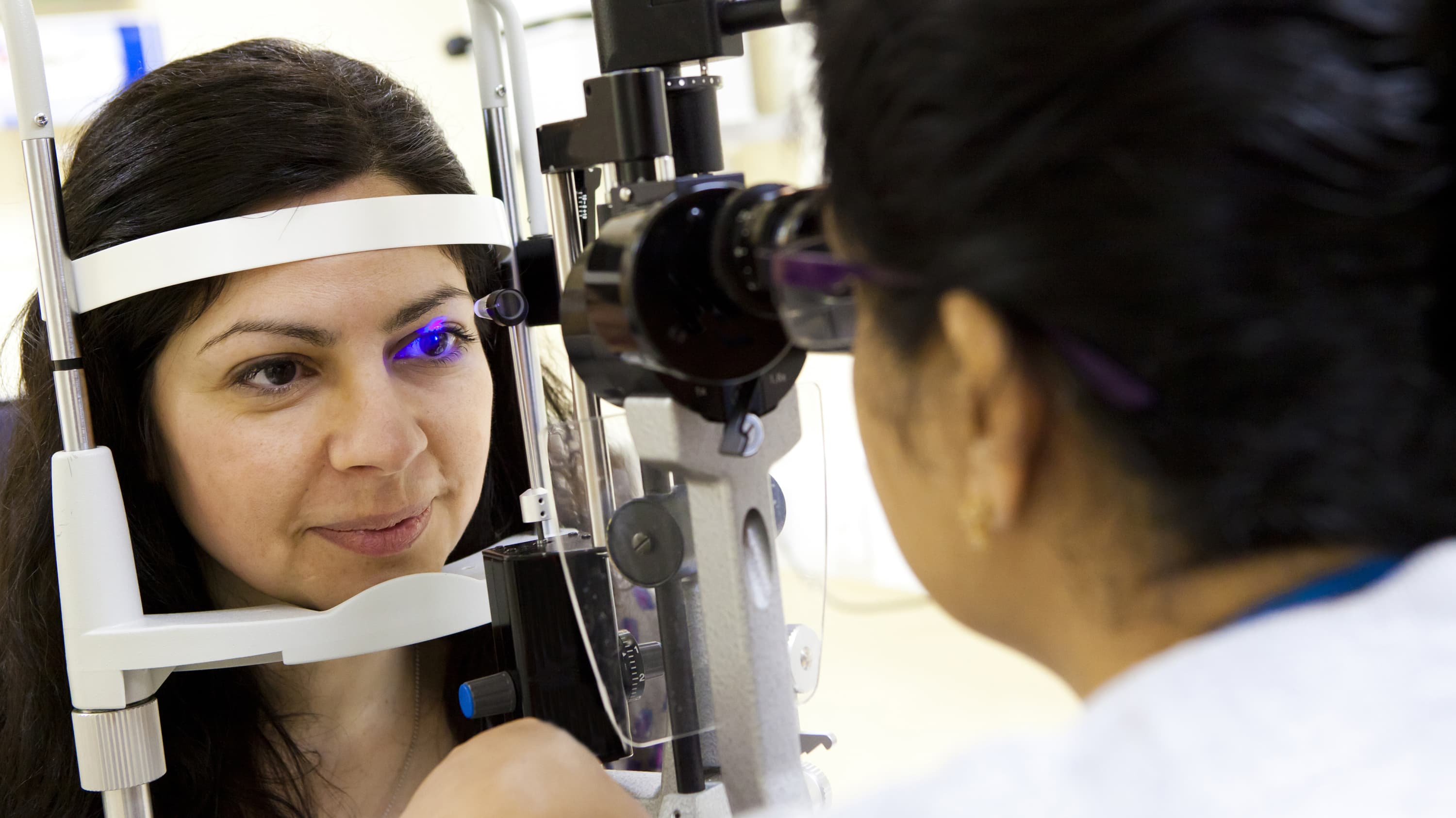 A woman has an eye exam, possibly for glaucoma