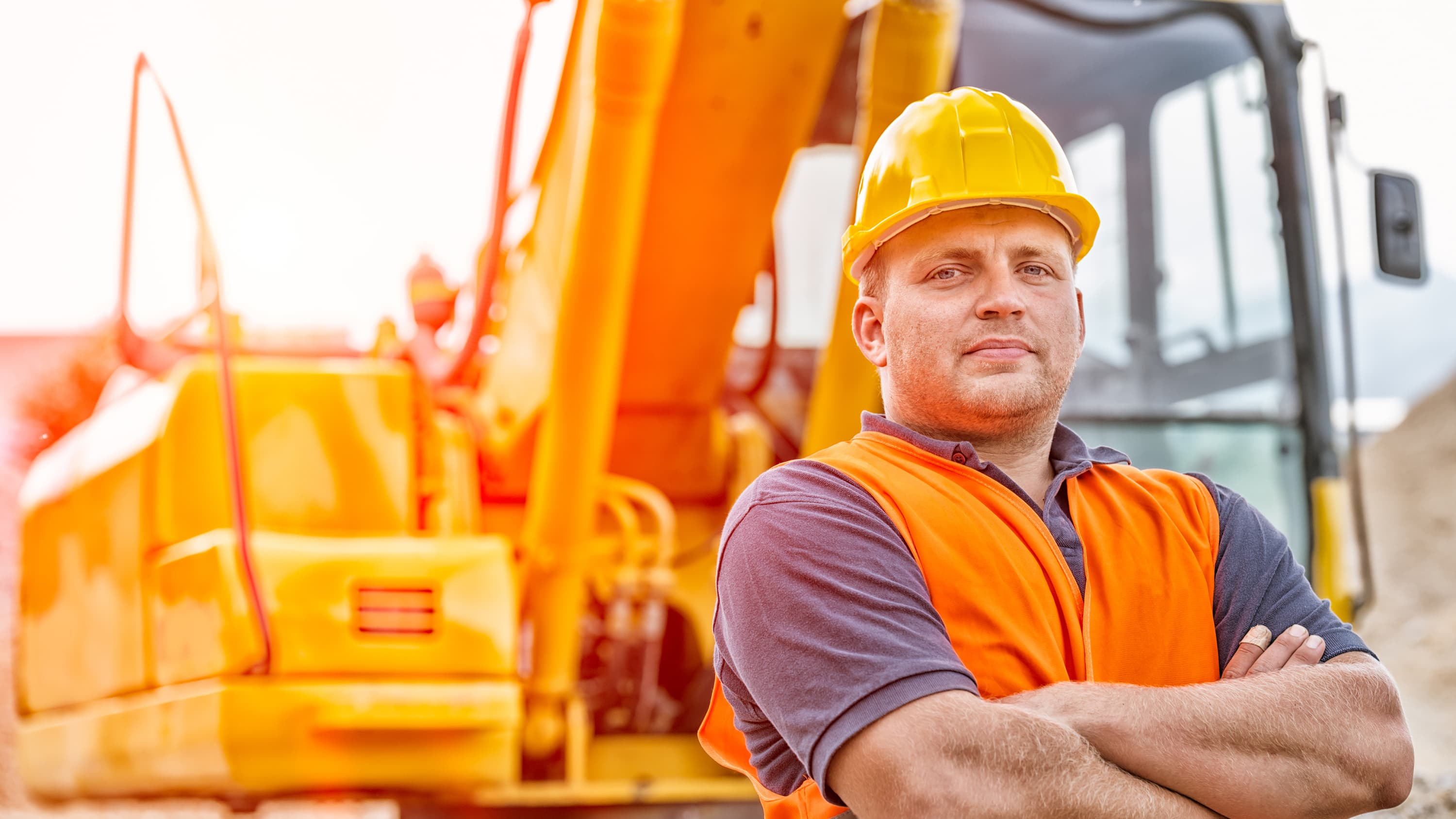 A construction worker who suffers from sleep apnea stands near his vehicle with his arms folded