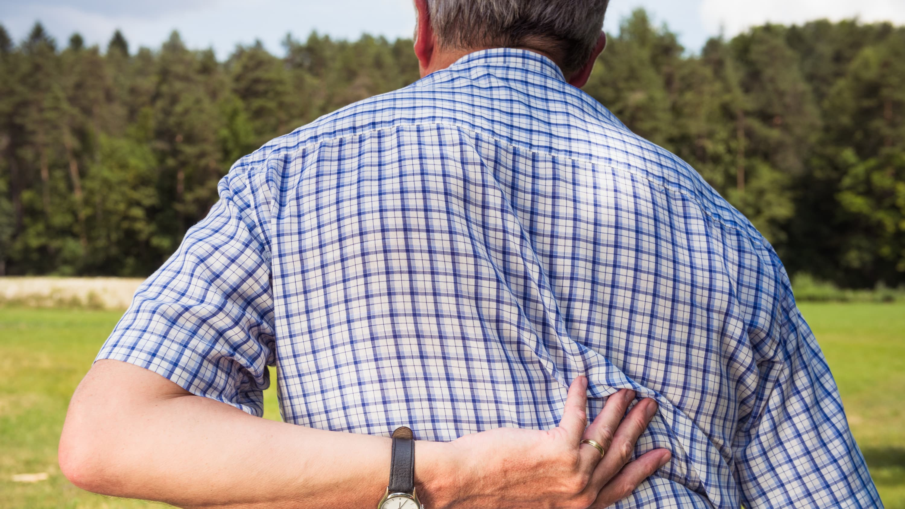 A man with a degenerative and rheumatologic spinal disorder presses his hand against his back.