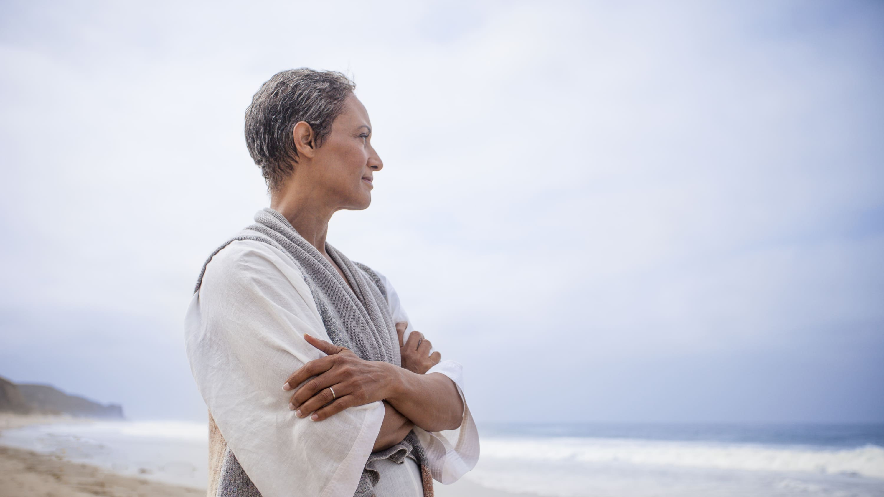 A woman standing on a beach looks out on the ocean, possibly thinking about pancreatic surgery.