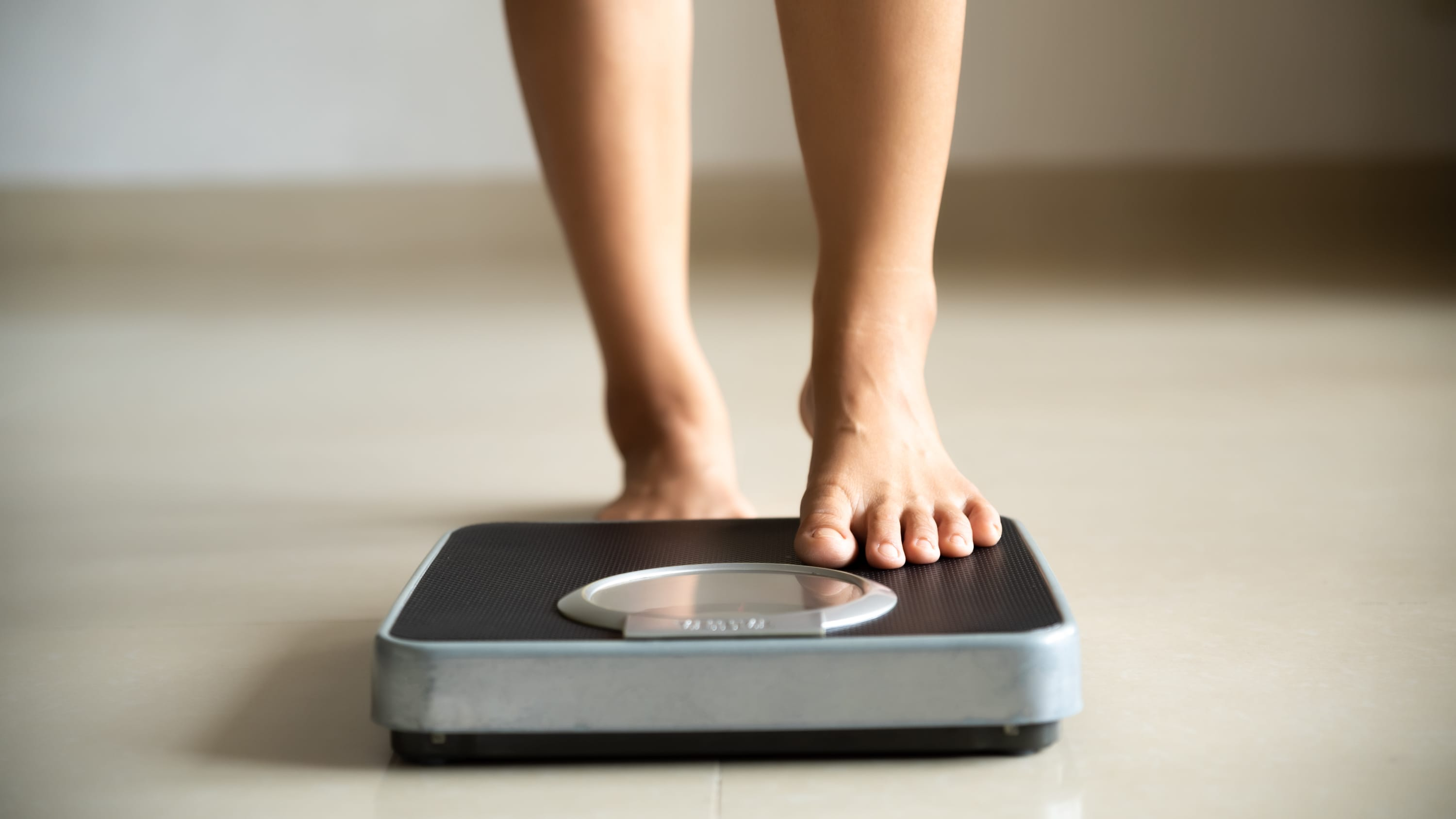 woman stepping on the scale, hoping for weight loss