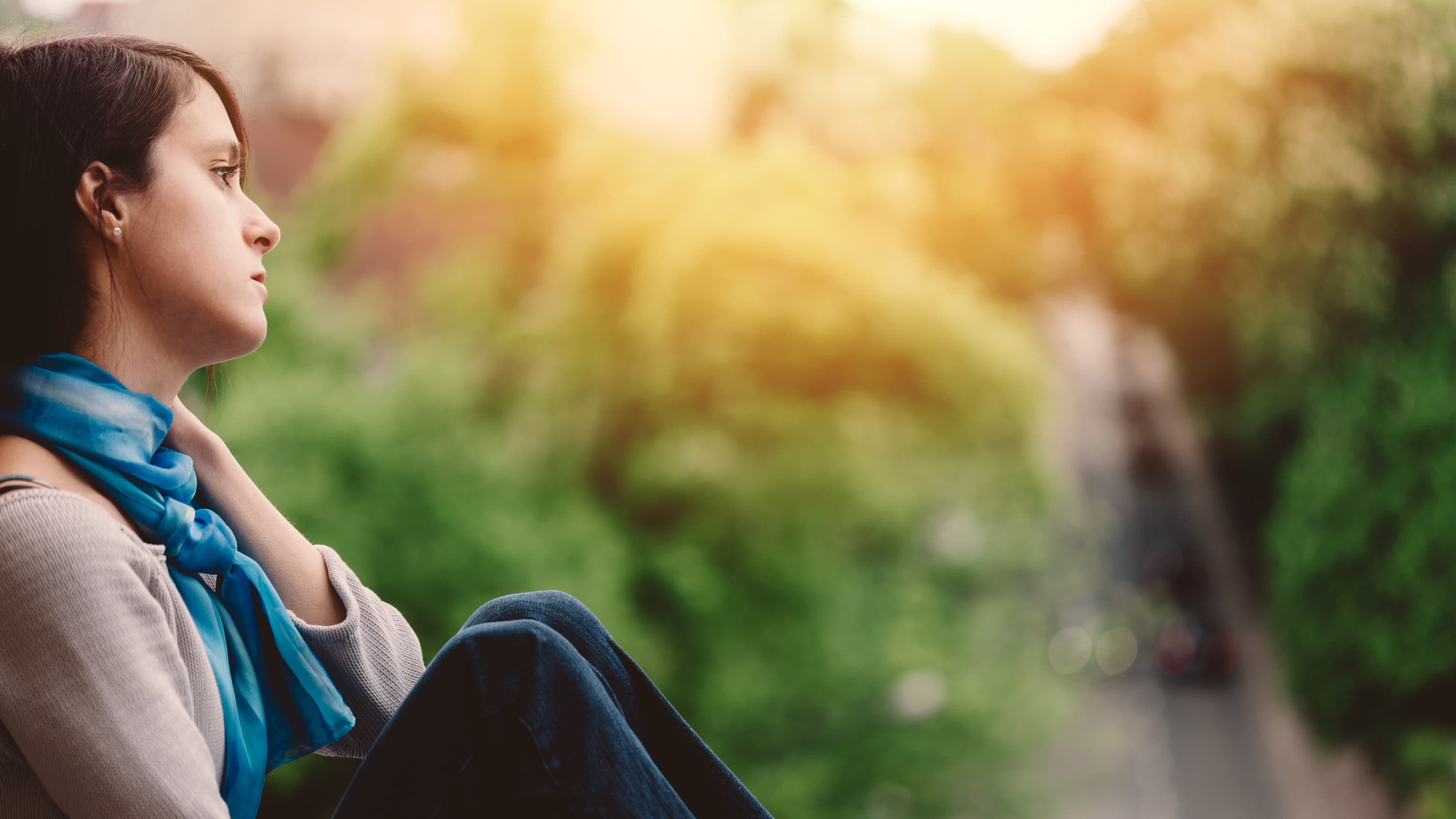 A young woman who is feeling suicidal sits alone outside.