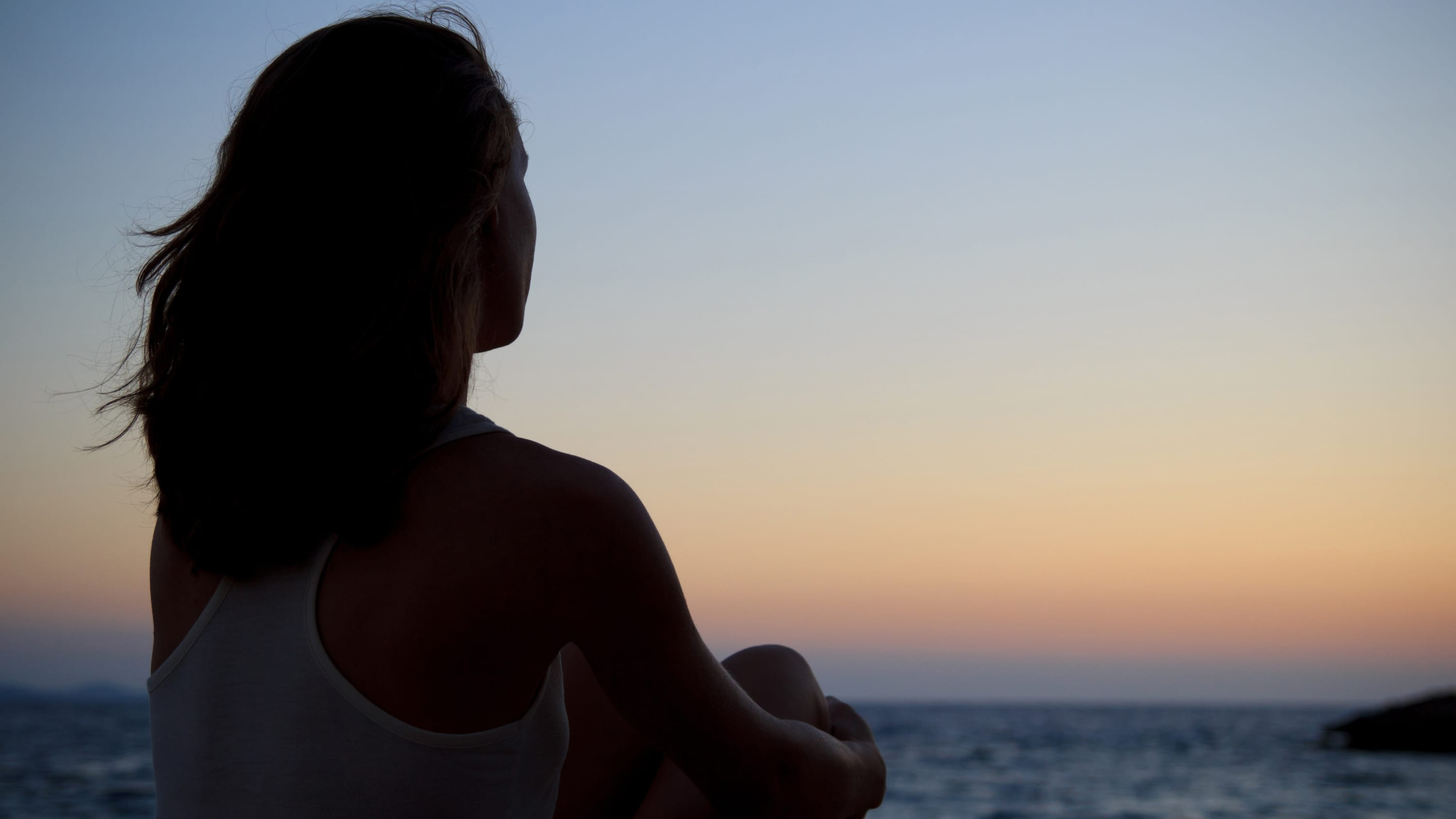 A woman with breast cancer with back to the audience, looking into sunset.