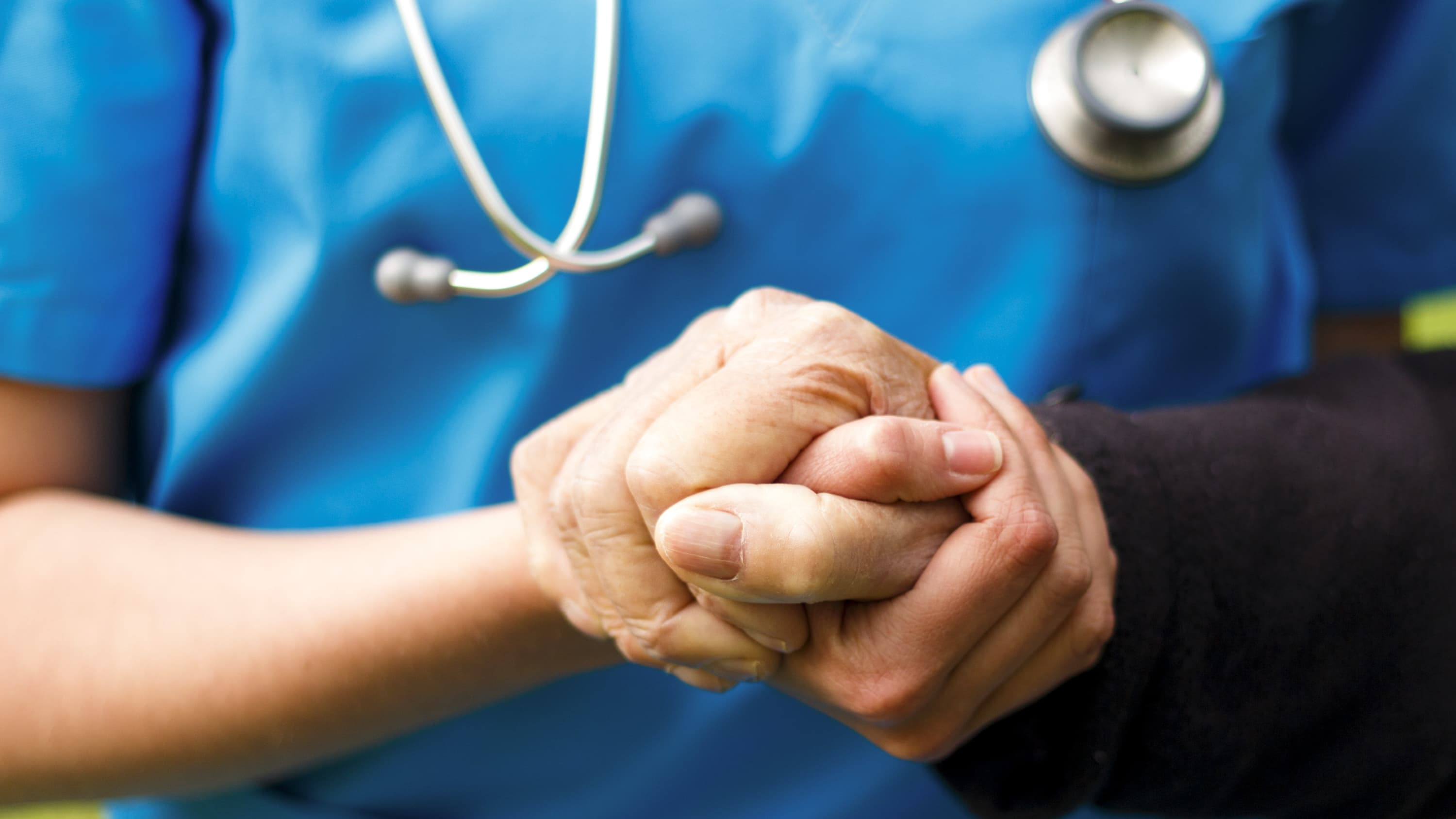 A doctor holds the hand of a patient with Parkinson's