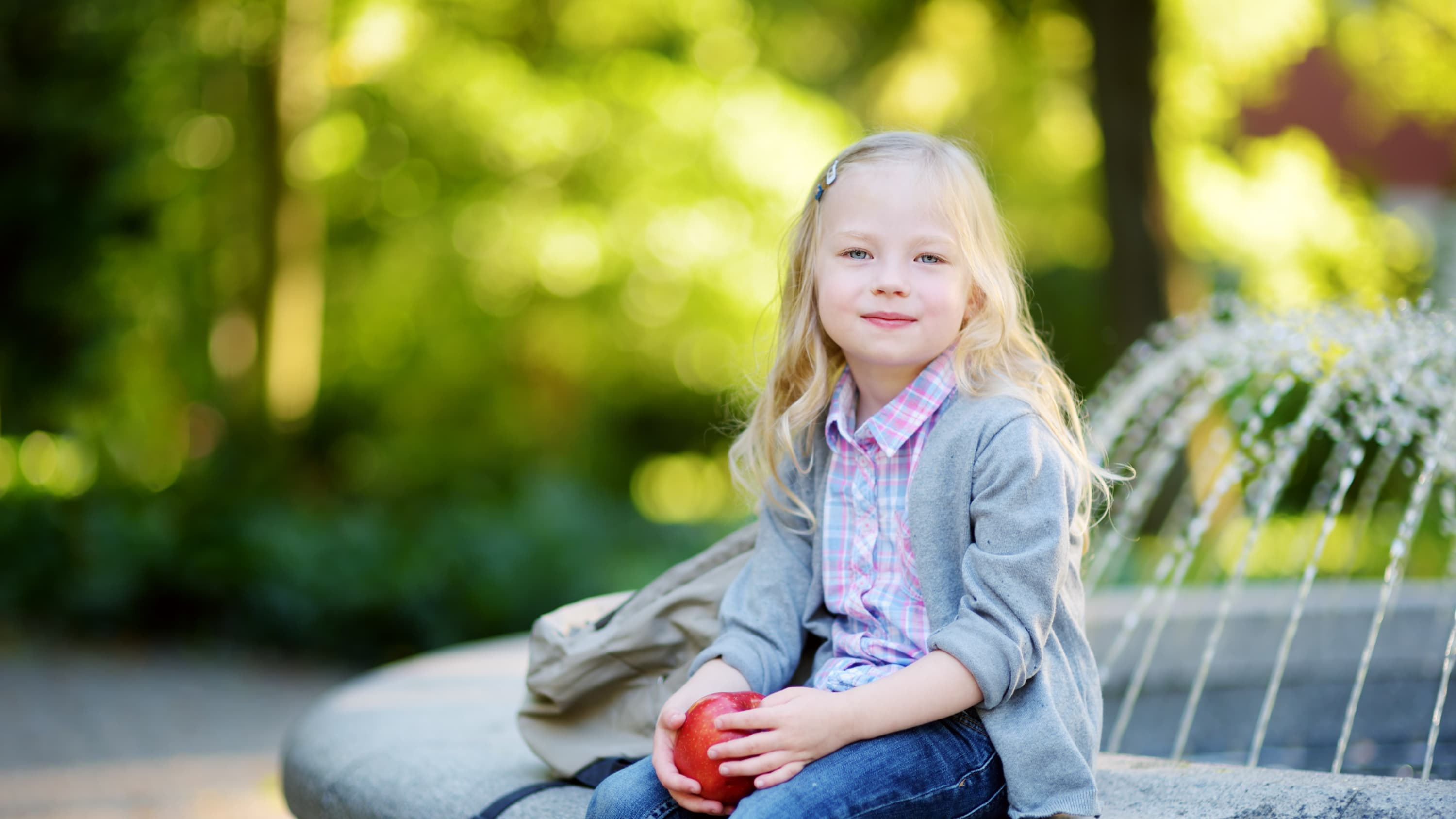 A girl, who could be a pediatric cancer survivor, is sitting on a the edge of a park fountain with an apple in her hand.