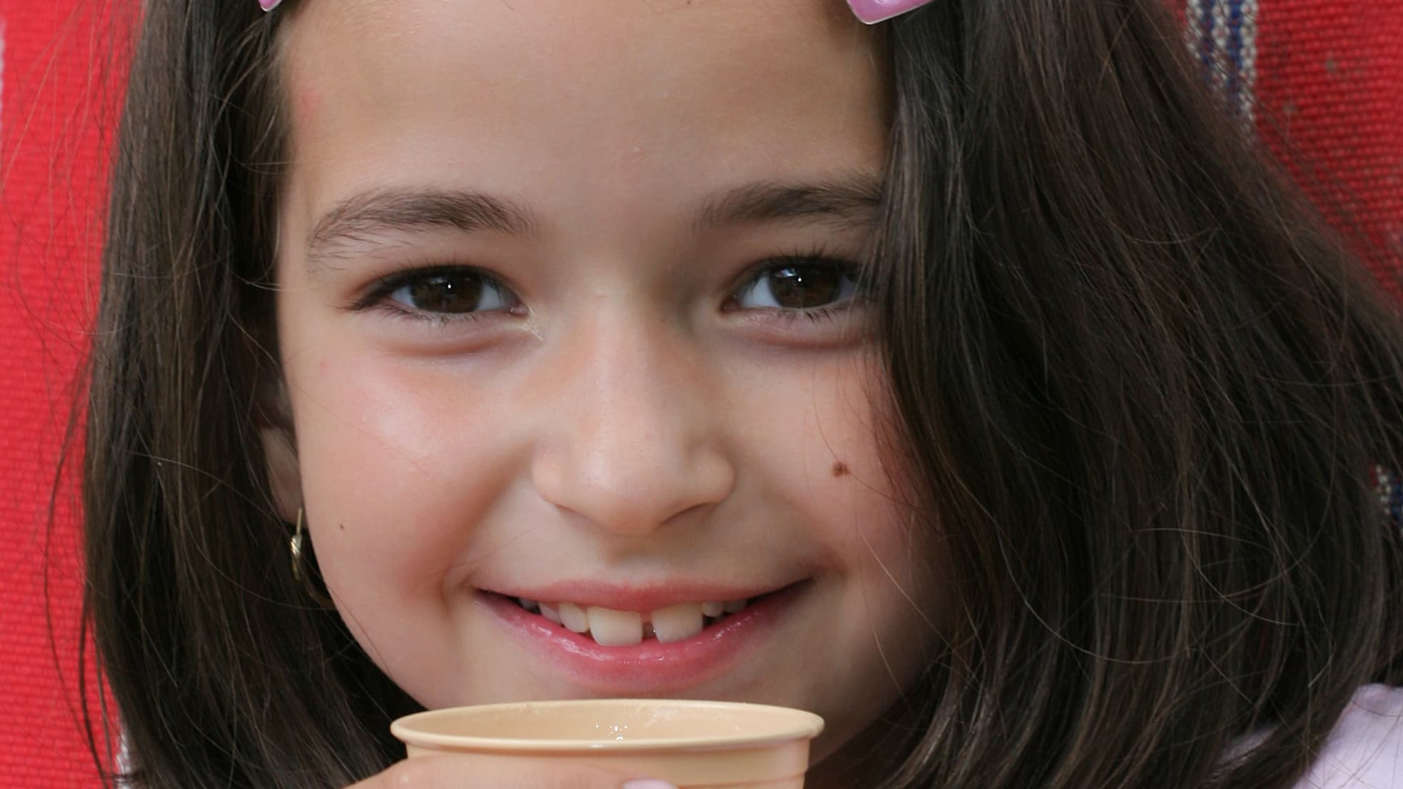 A girl who may have a congenital hand condition holds a cup.