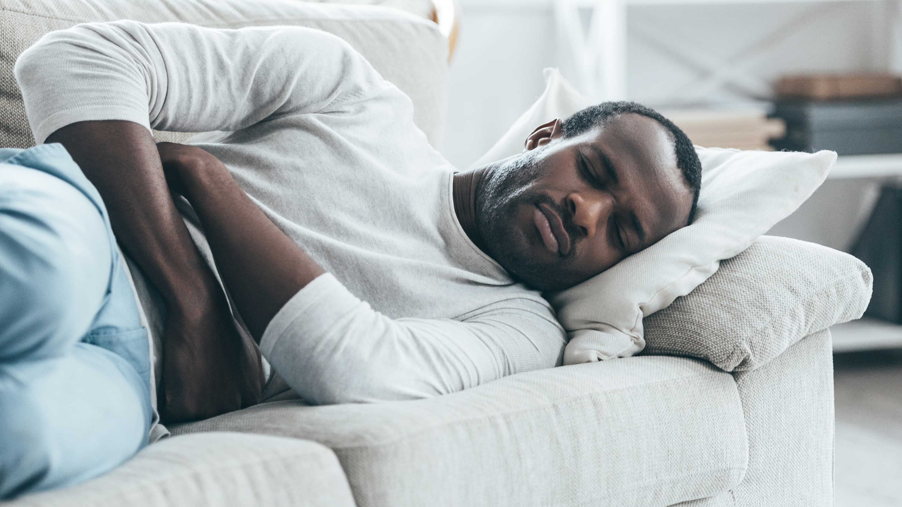 A man lays on a white couch holding his stomach possibly before a diagnosis of pancreatic cancer.