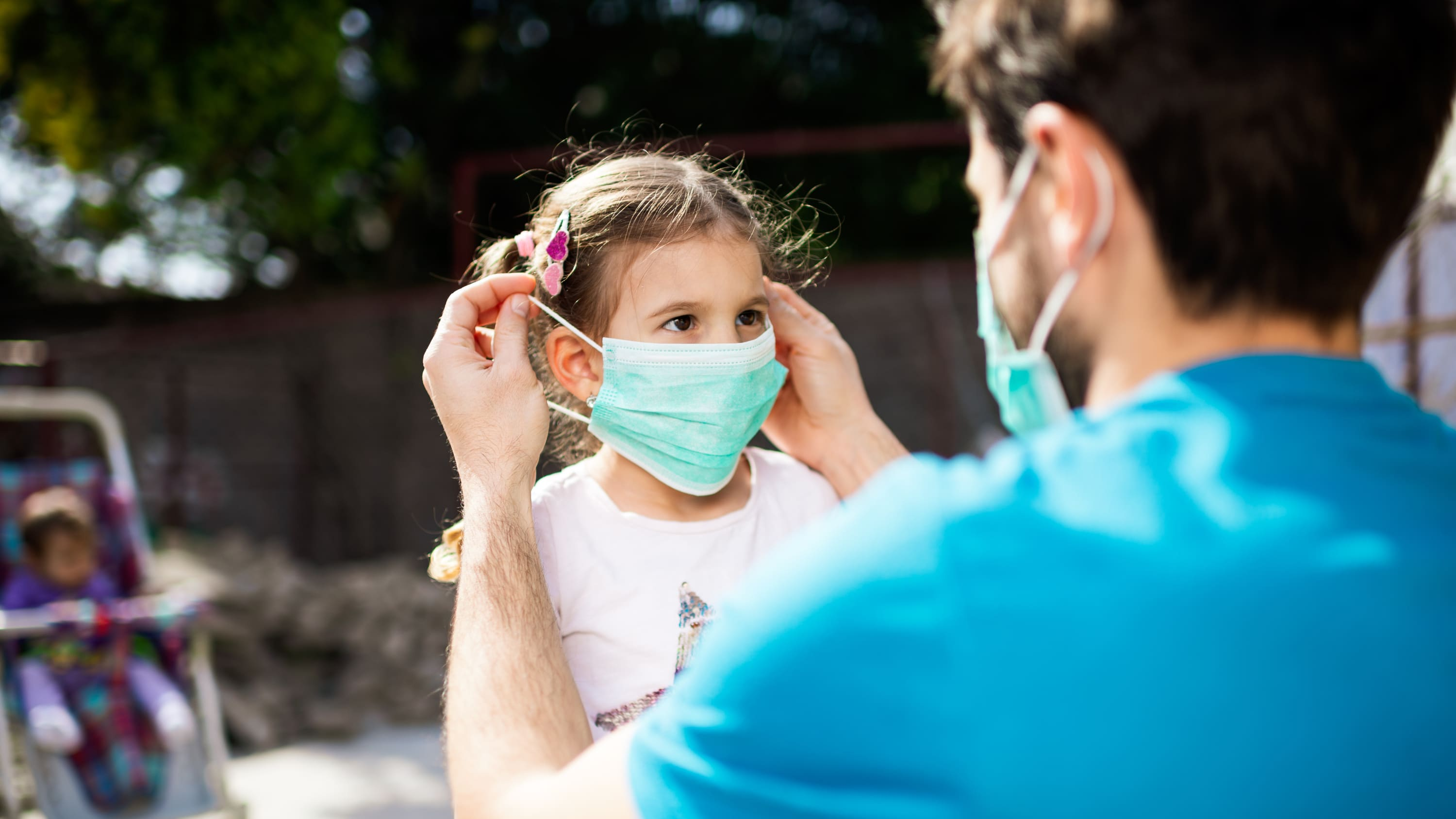 father putting mask on his daughter, possibly to protect against covid-19-related PMIS