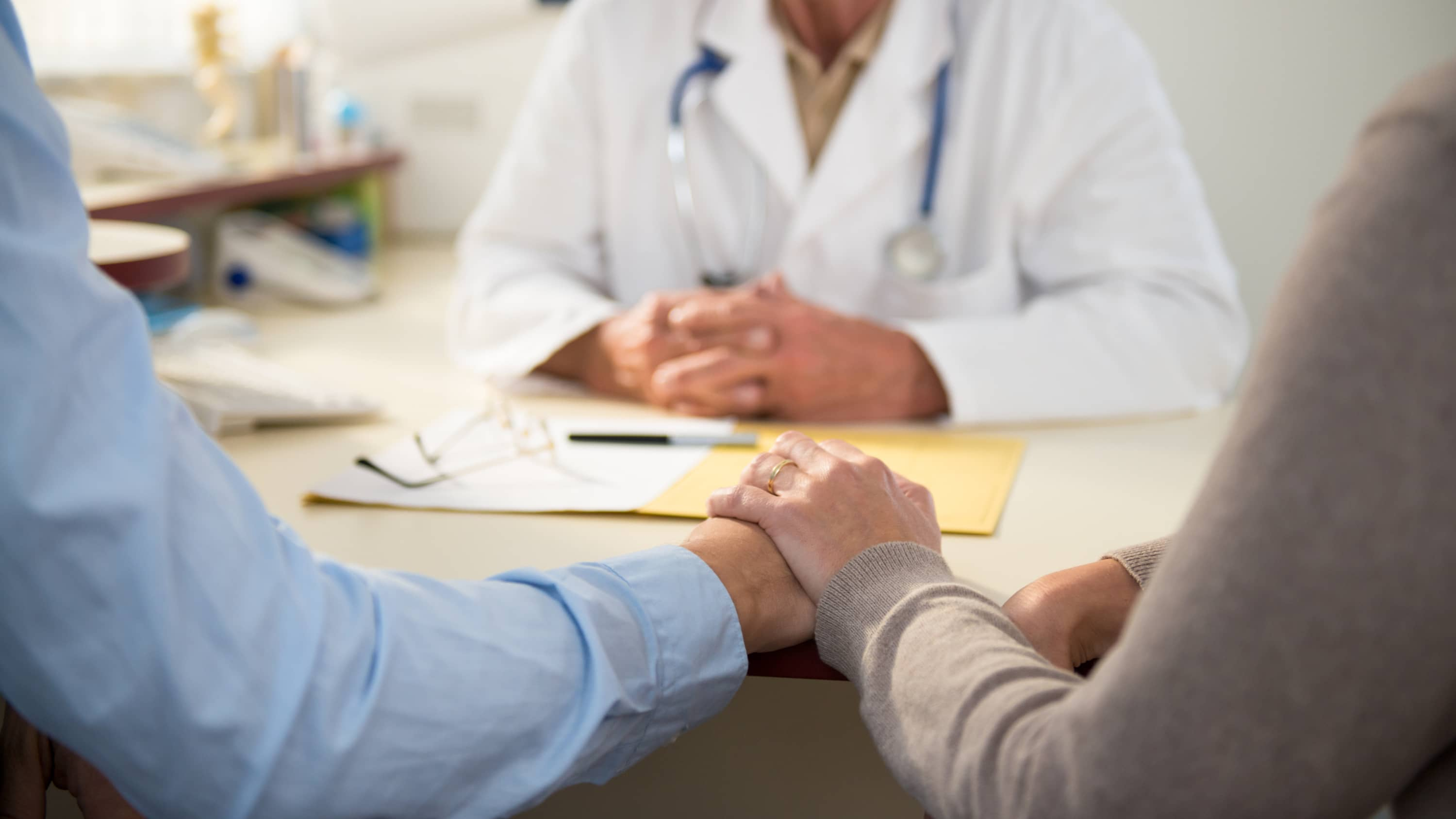 A couple holding hands talks to a doctor about imaging results.