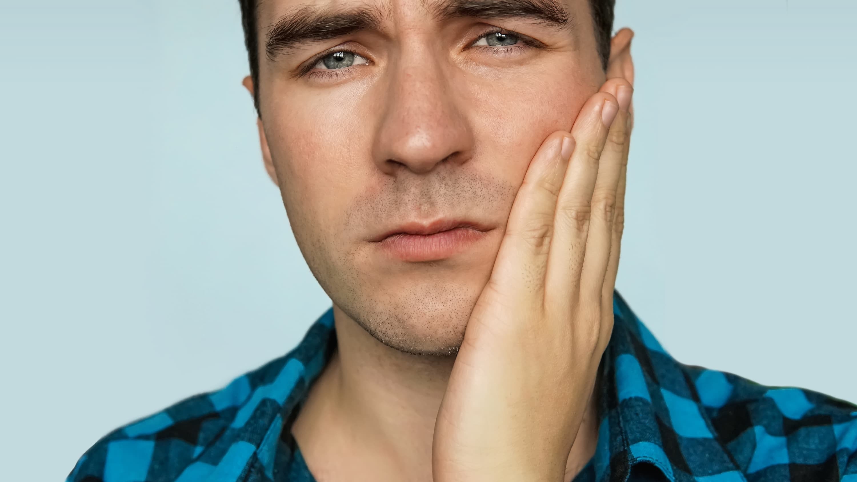 A man with trigeminal neuralgia touching his jaw who is in pain.