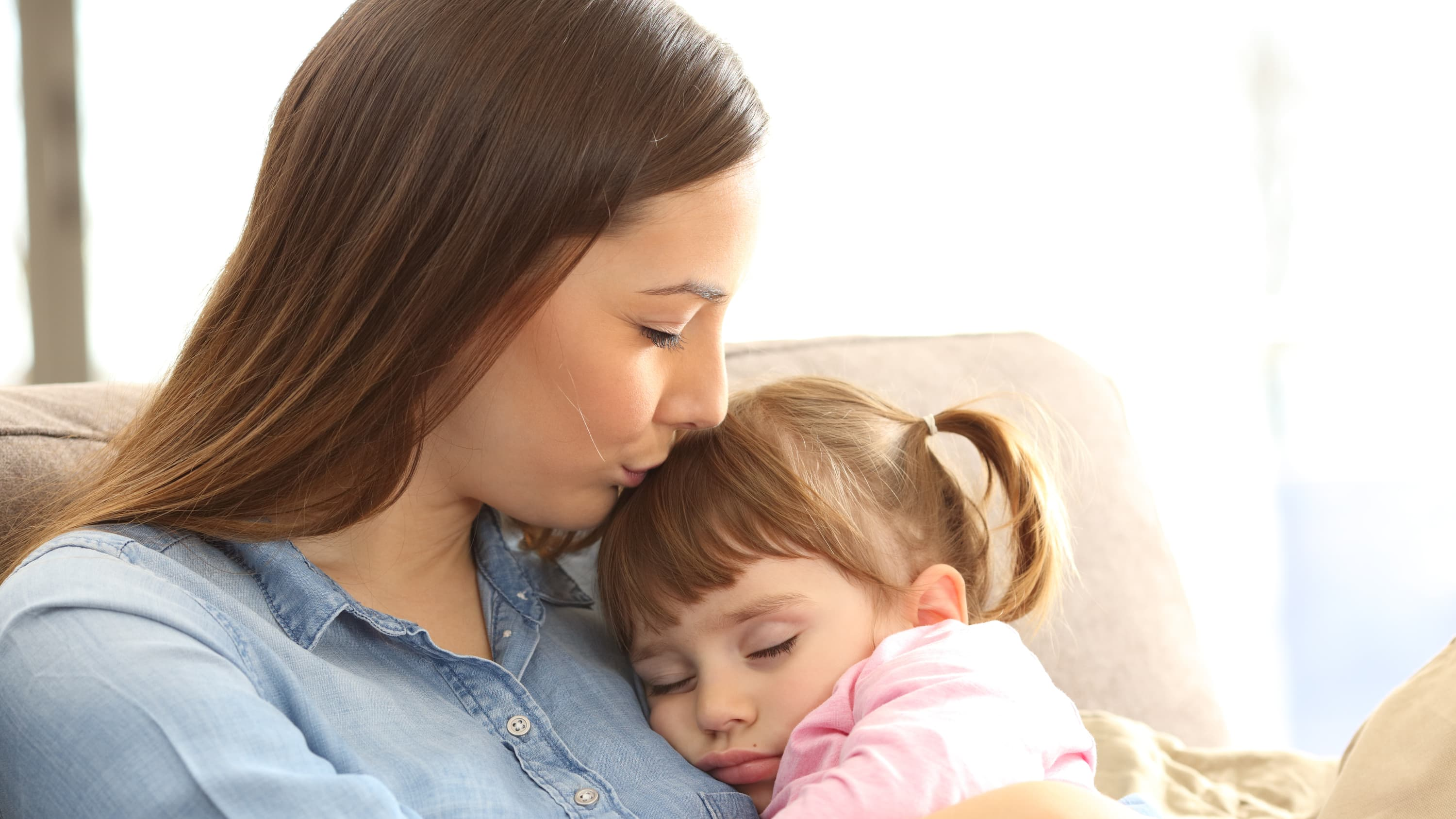 Close up portrait of a mother kissing her young daughter, who possibly has pediatric asthma.