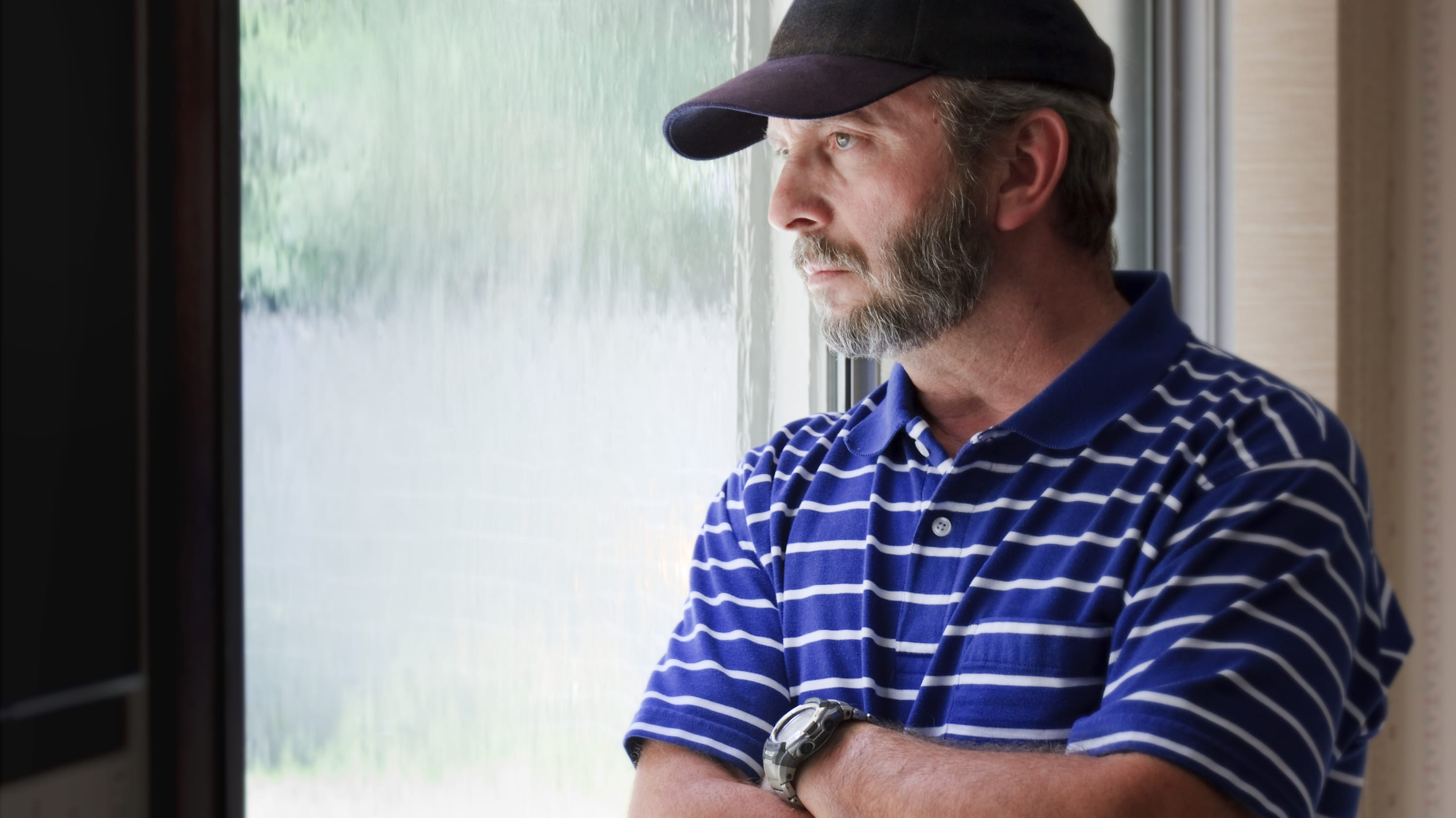Adult male looking out a rain covered window looking concerned, possibly about a gambling disorder