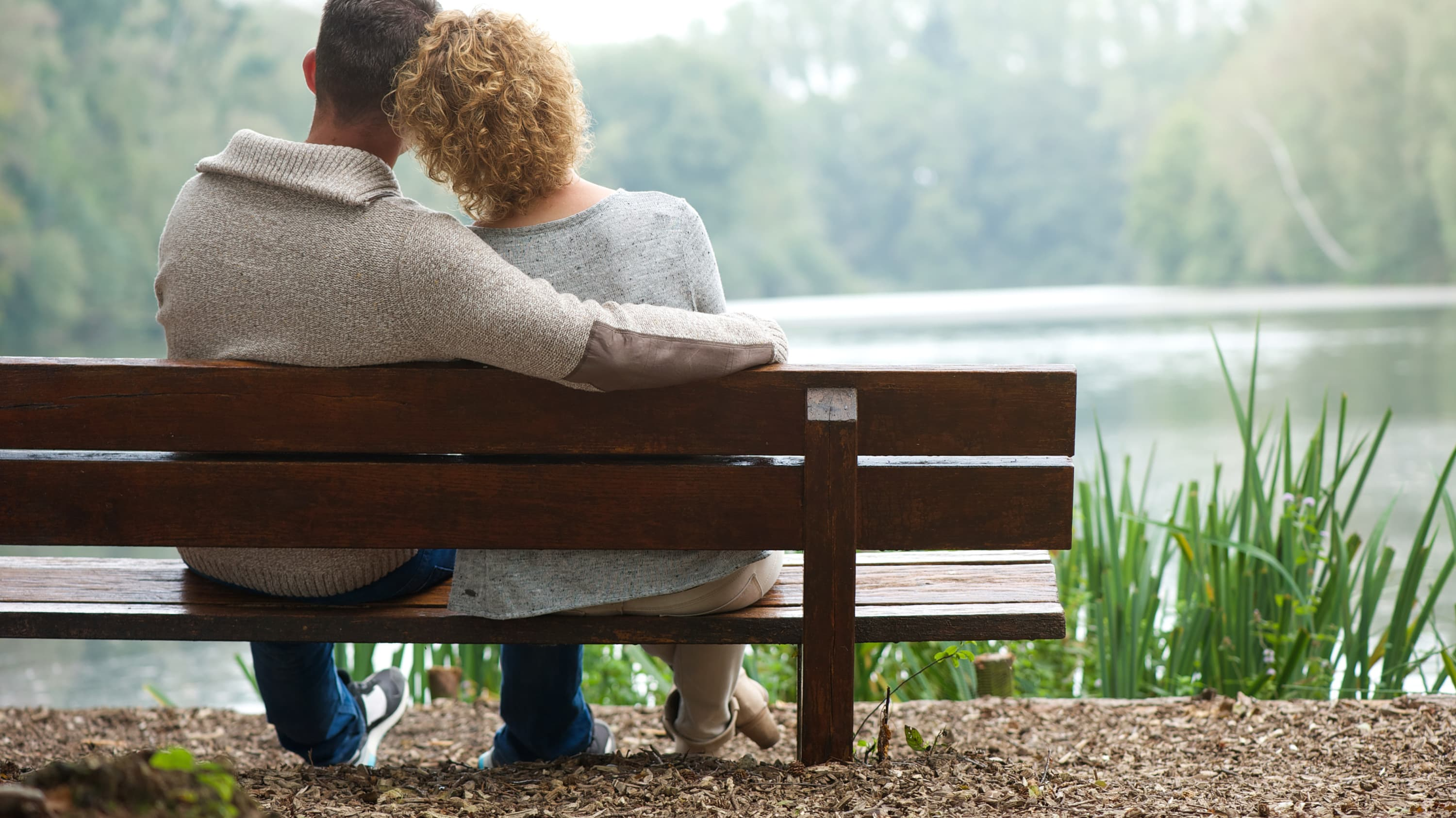 A couple sits and thinks on a park bench, considering female infertility