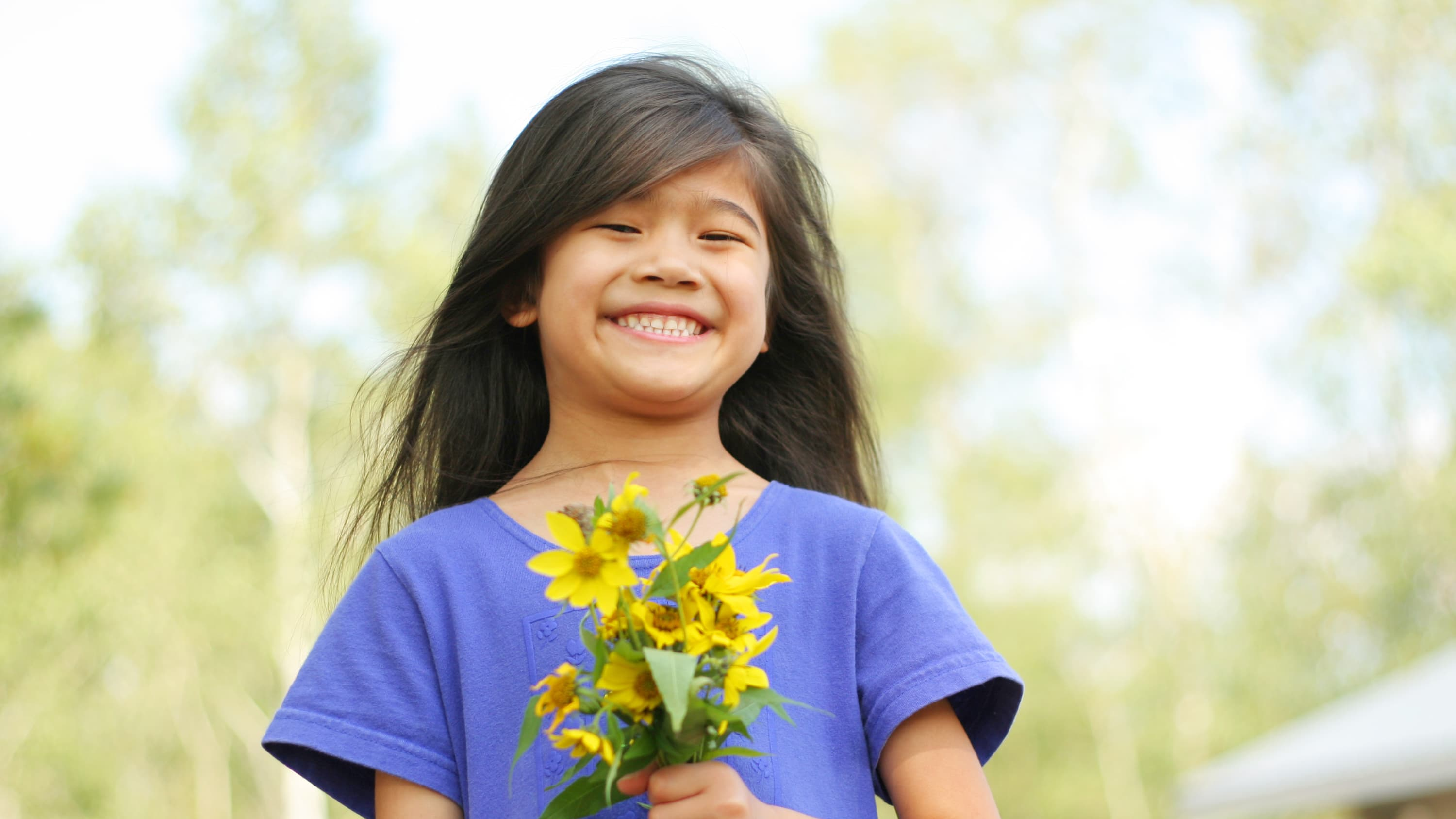 A young girl with epilepsy smiles for the camera while holding flowers.