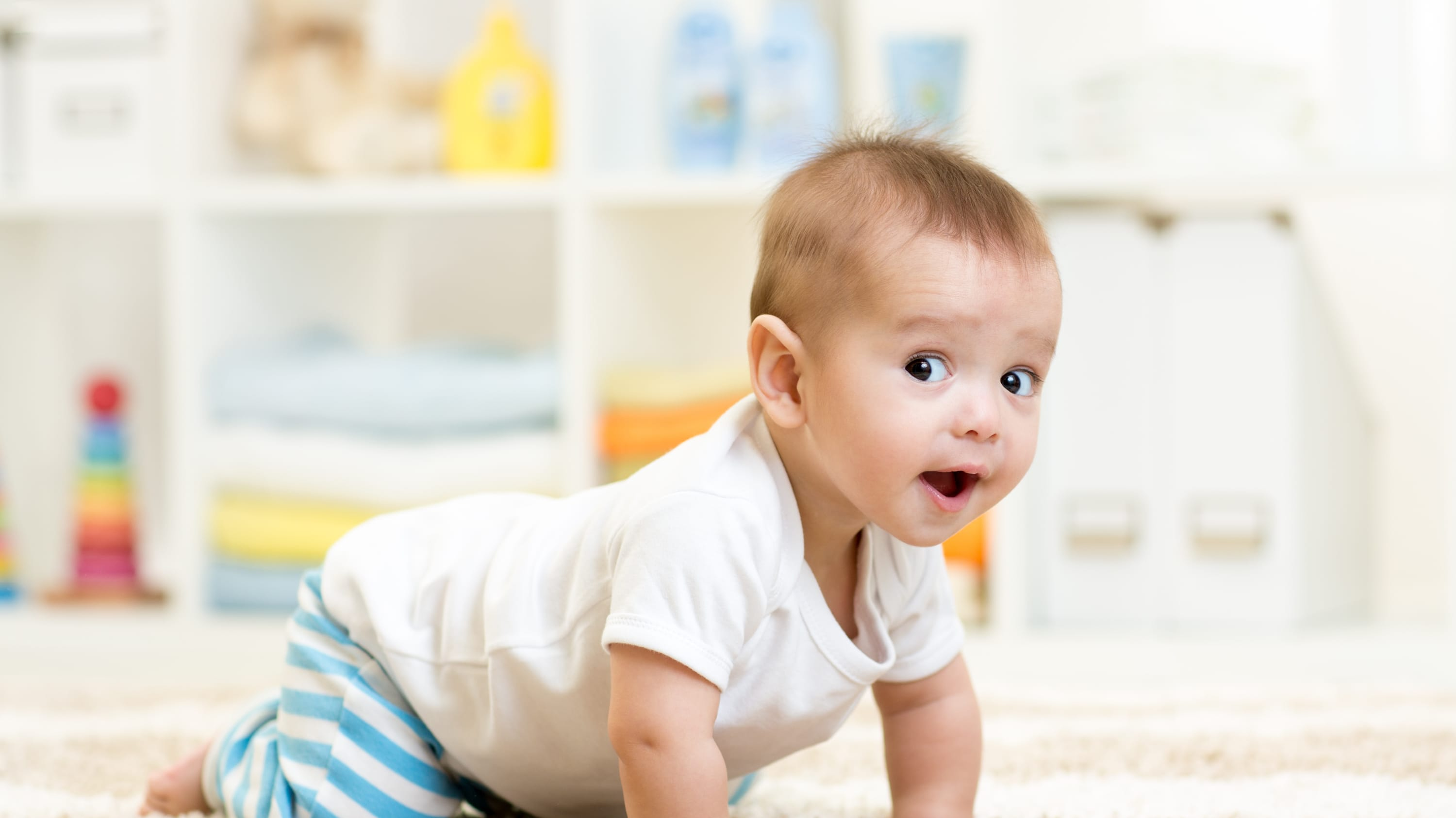 An infant who may have child development issues crawls on the floor.