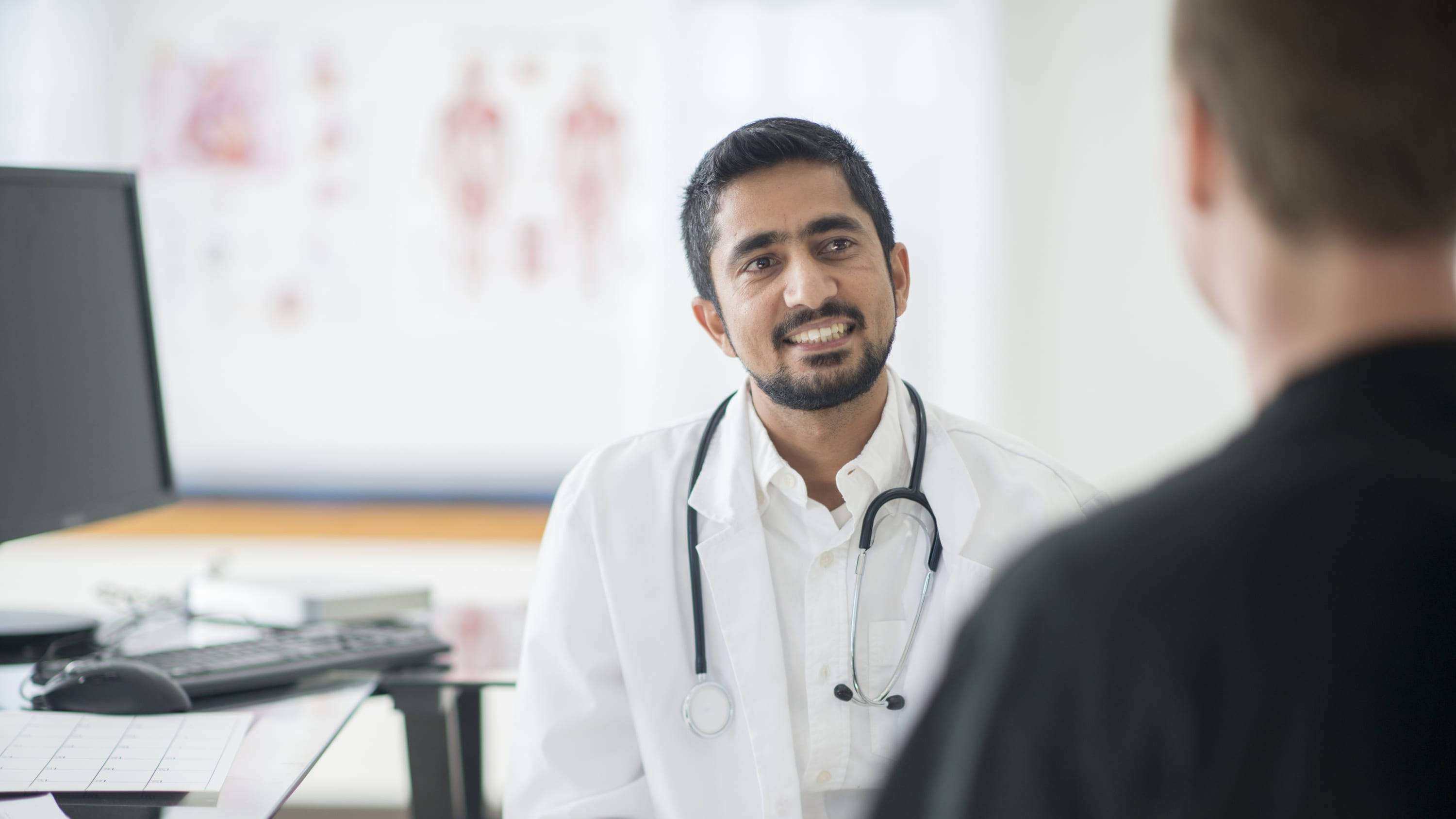 A portrait of a male doctor wearing a white coat who may be talking to a patient about radiation therapy for brain cancer.
