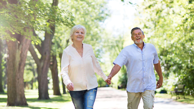 A senior couple walks outside wearing sunscreen to avoid melanoma.