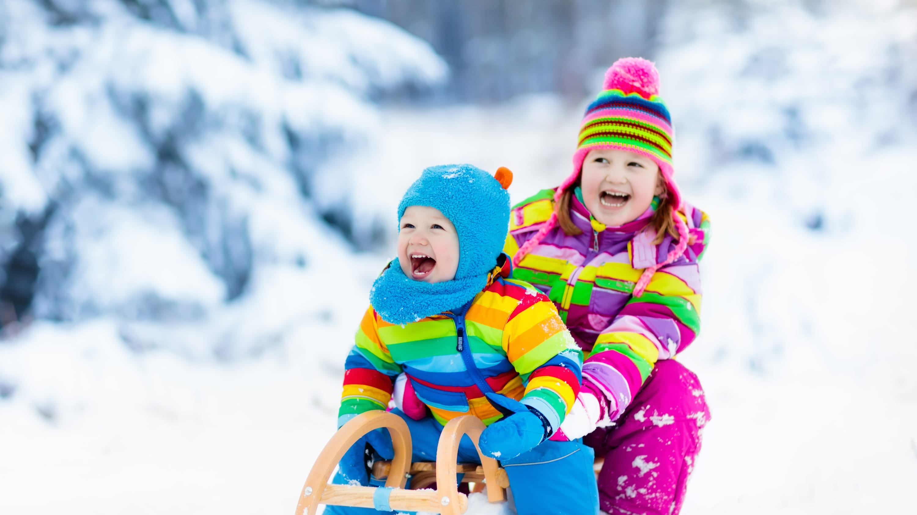 Two children are sledding while wearing colorful outerwear.