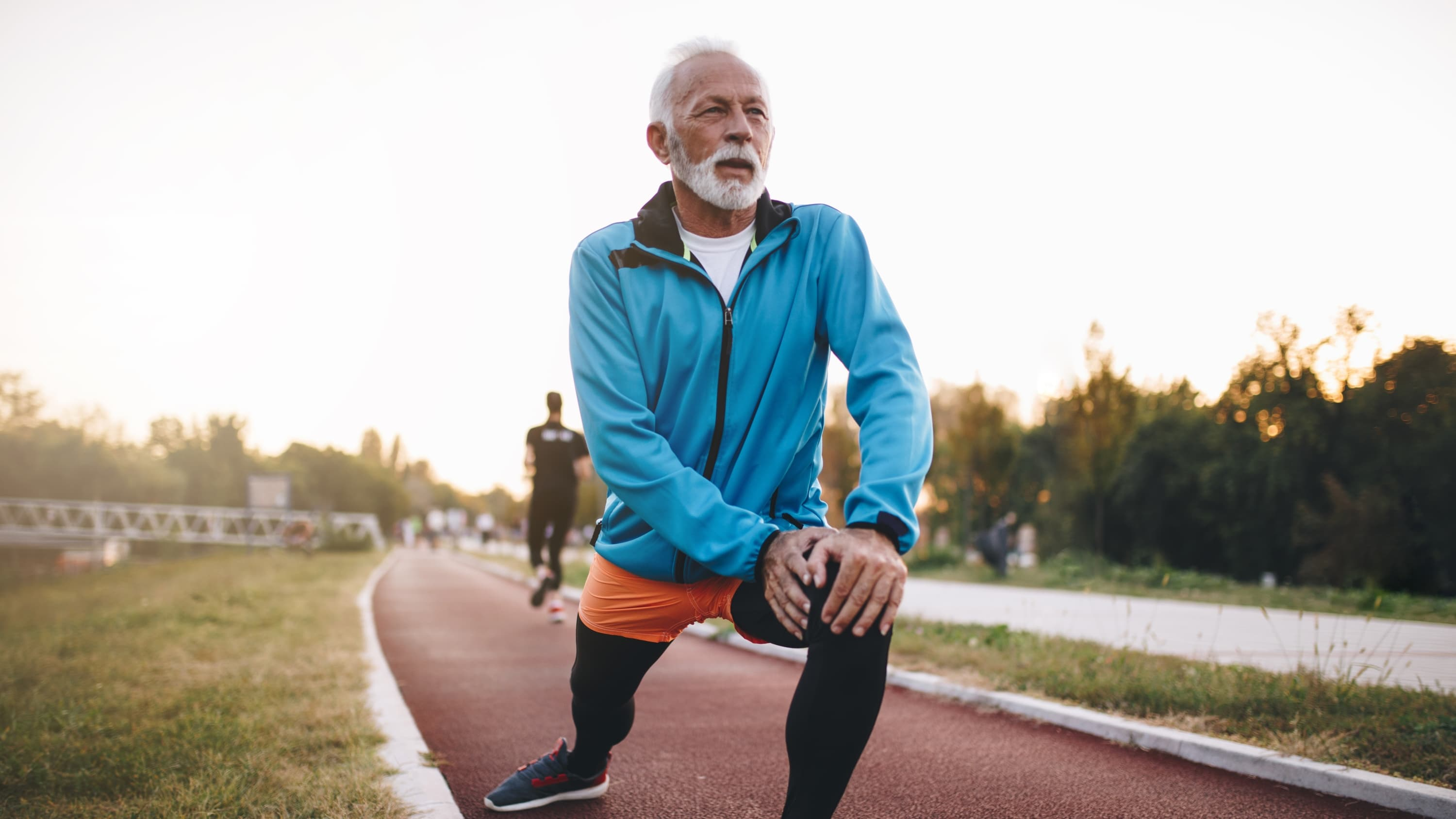 A senior man who may have had his heart checked with an echocardiogram is now stretching before jogging