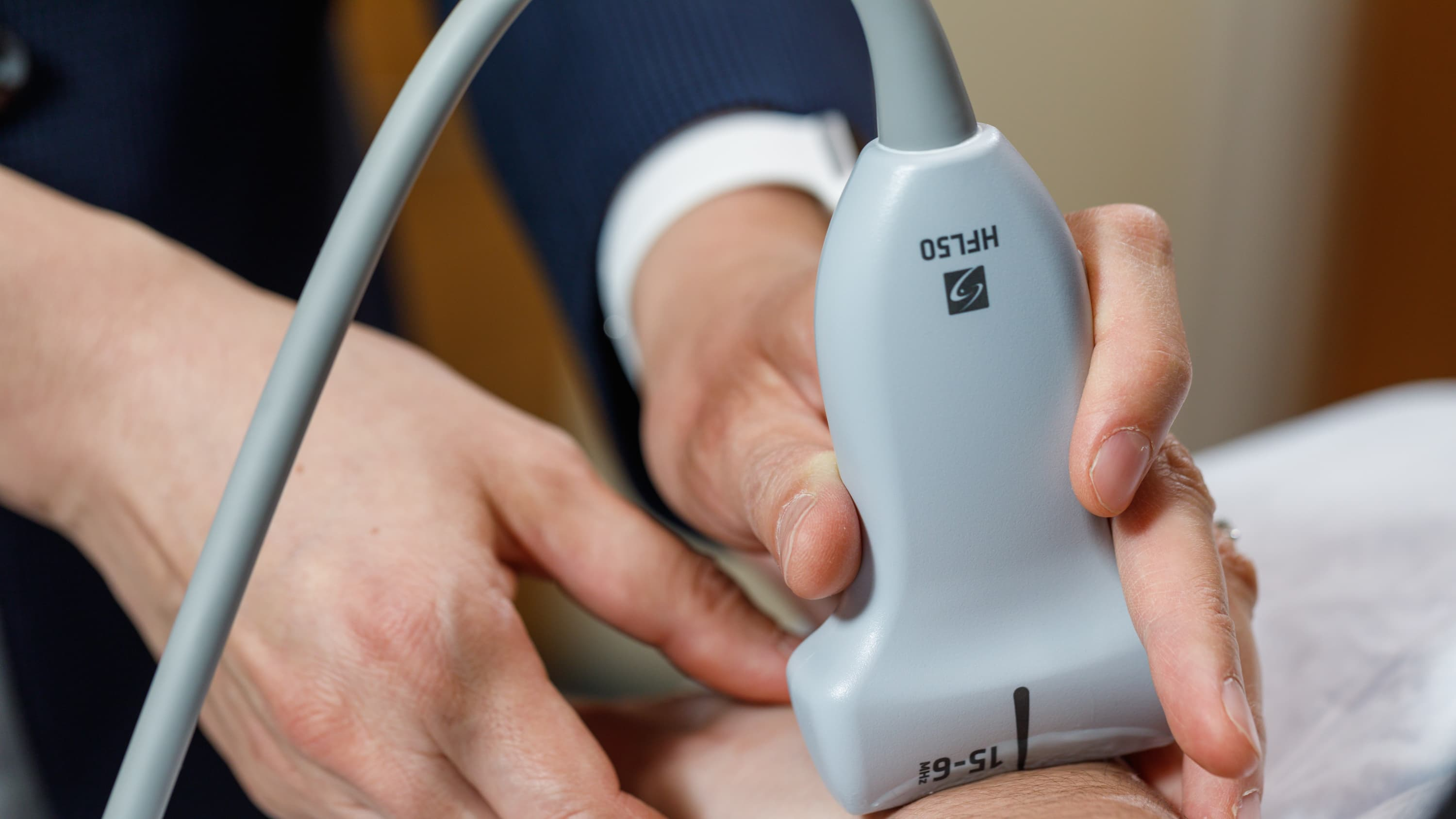 A doctor uses a muskuloskeletal ultrasound on a patient's wrist.