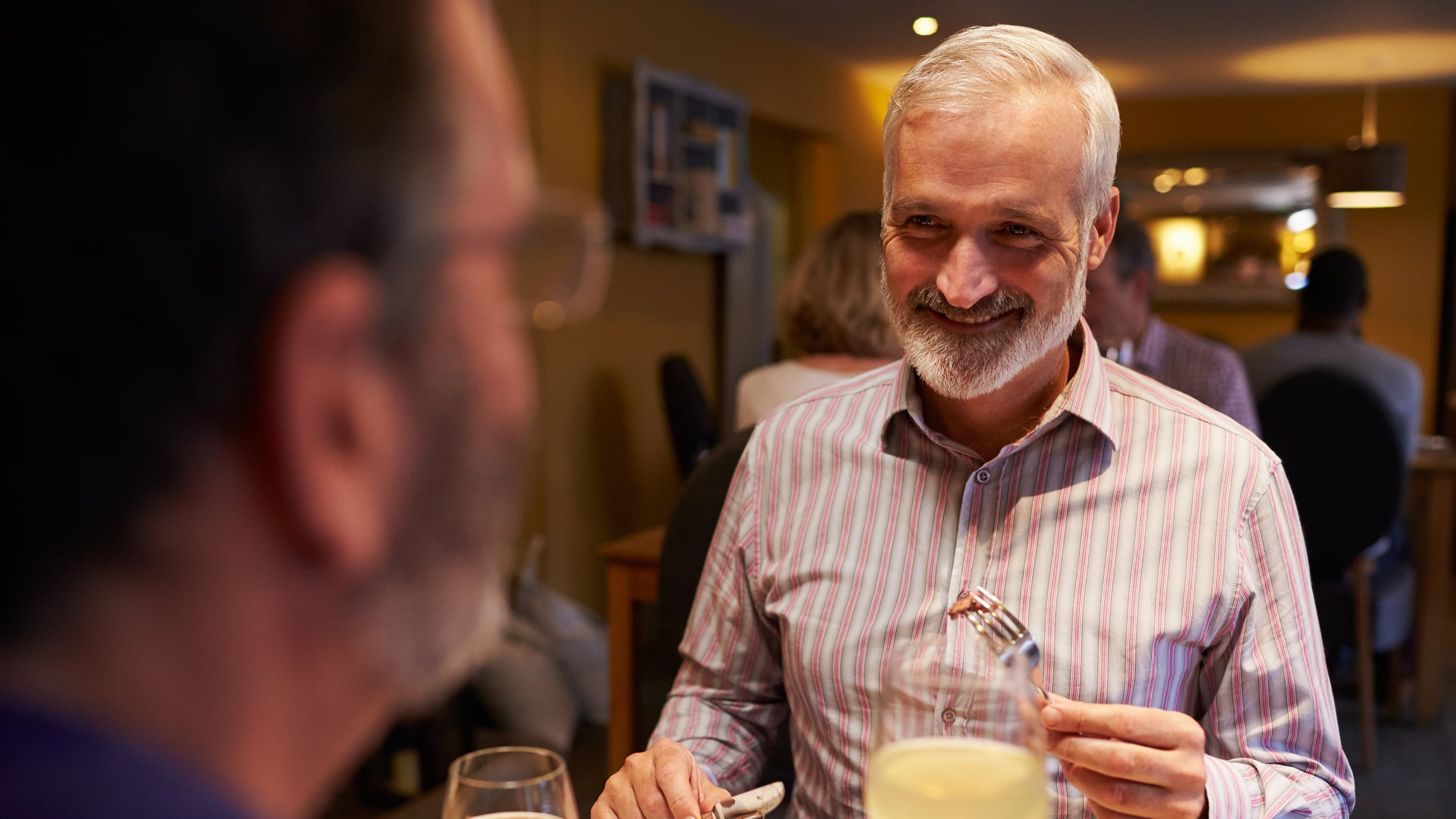 Man eating dinner, possibly discussing gastrointentinal cancers