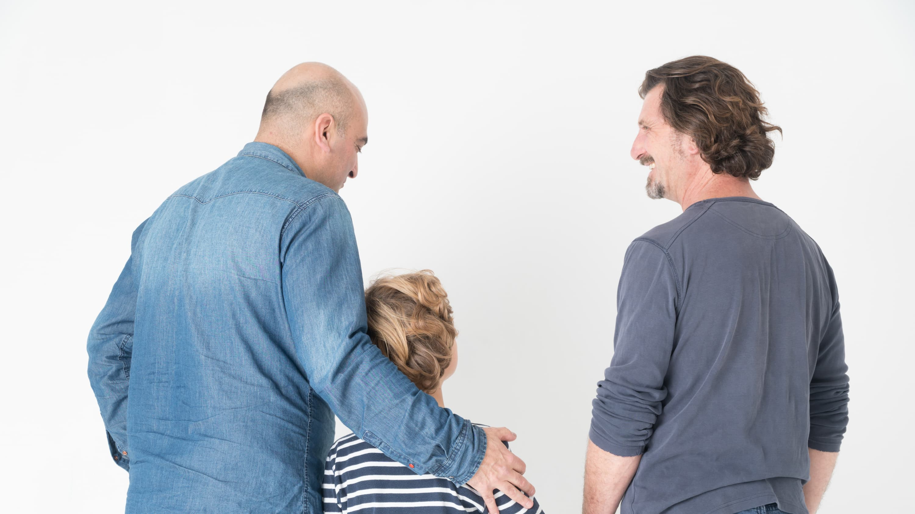 An older man and a younger man are walking with a child who has idiopathic short stature.