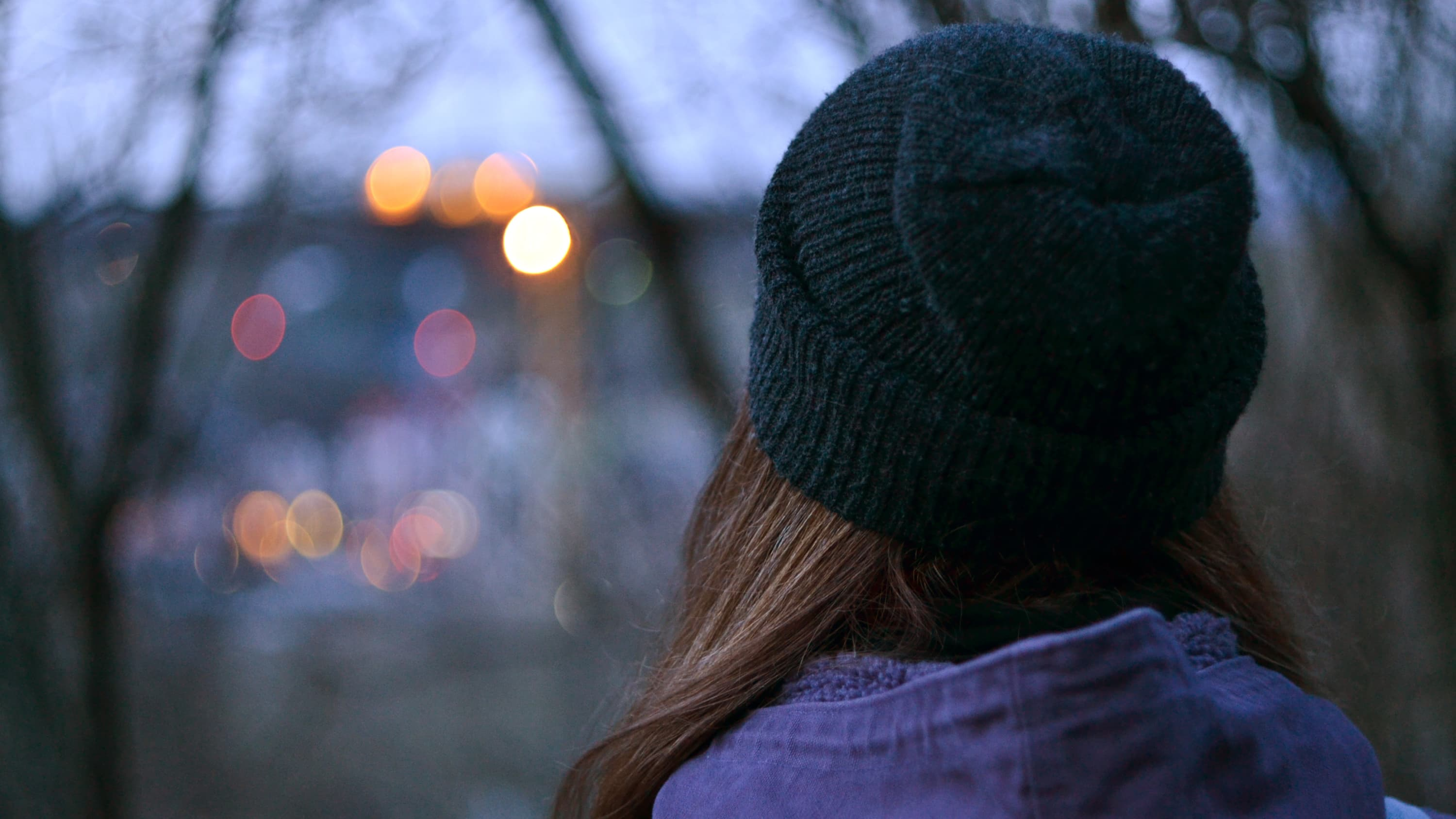A woman, who possibly has bipolar disorder, stands with her back to the camera at night