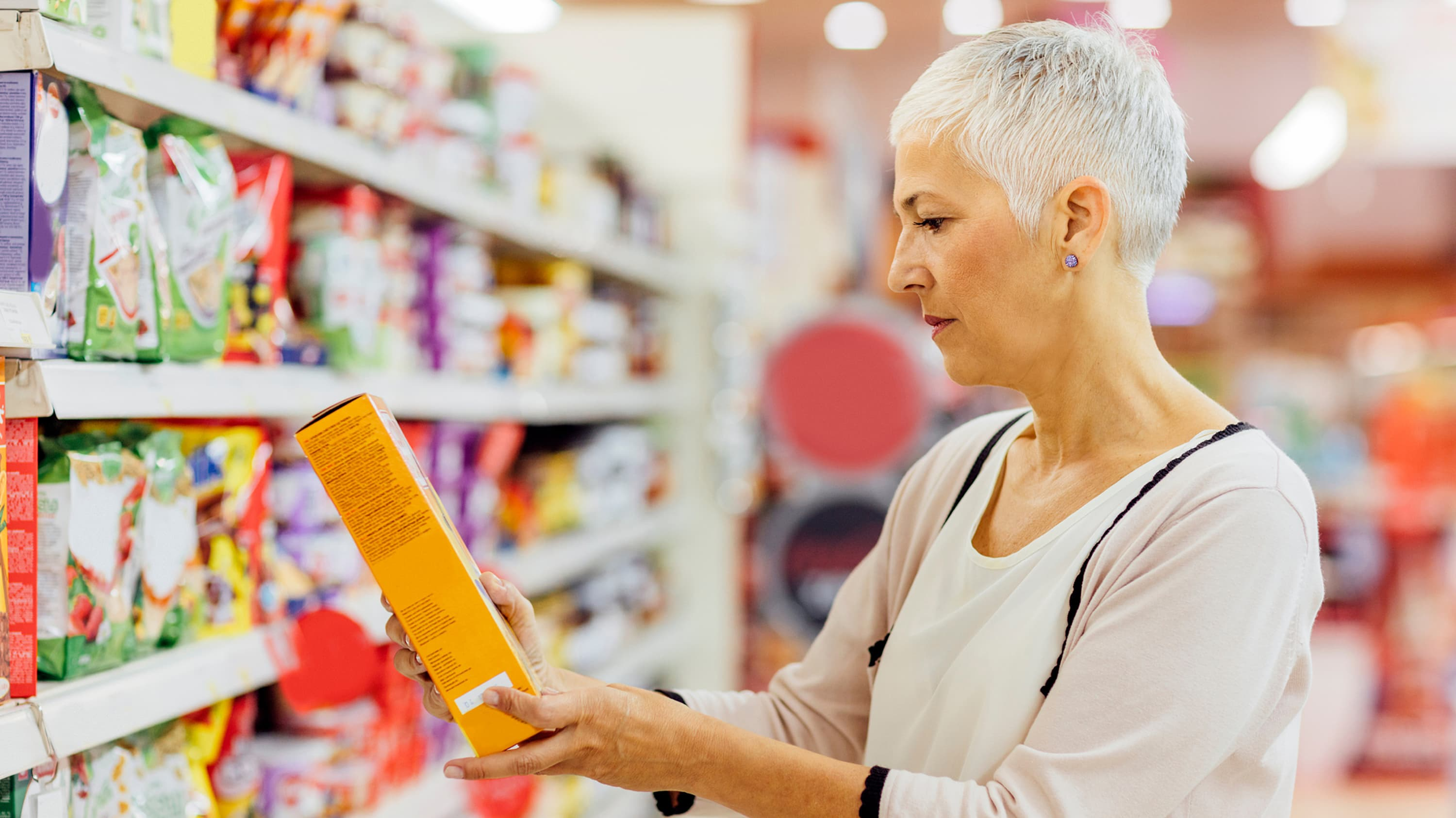 A woman examines a nutrition label, possibly for gluten.
