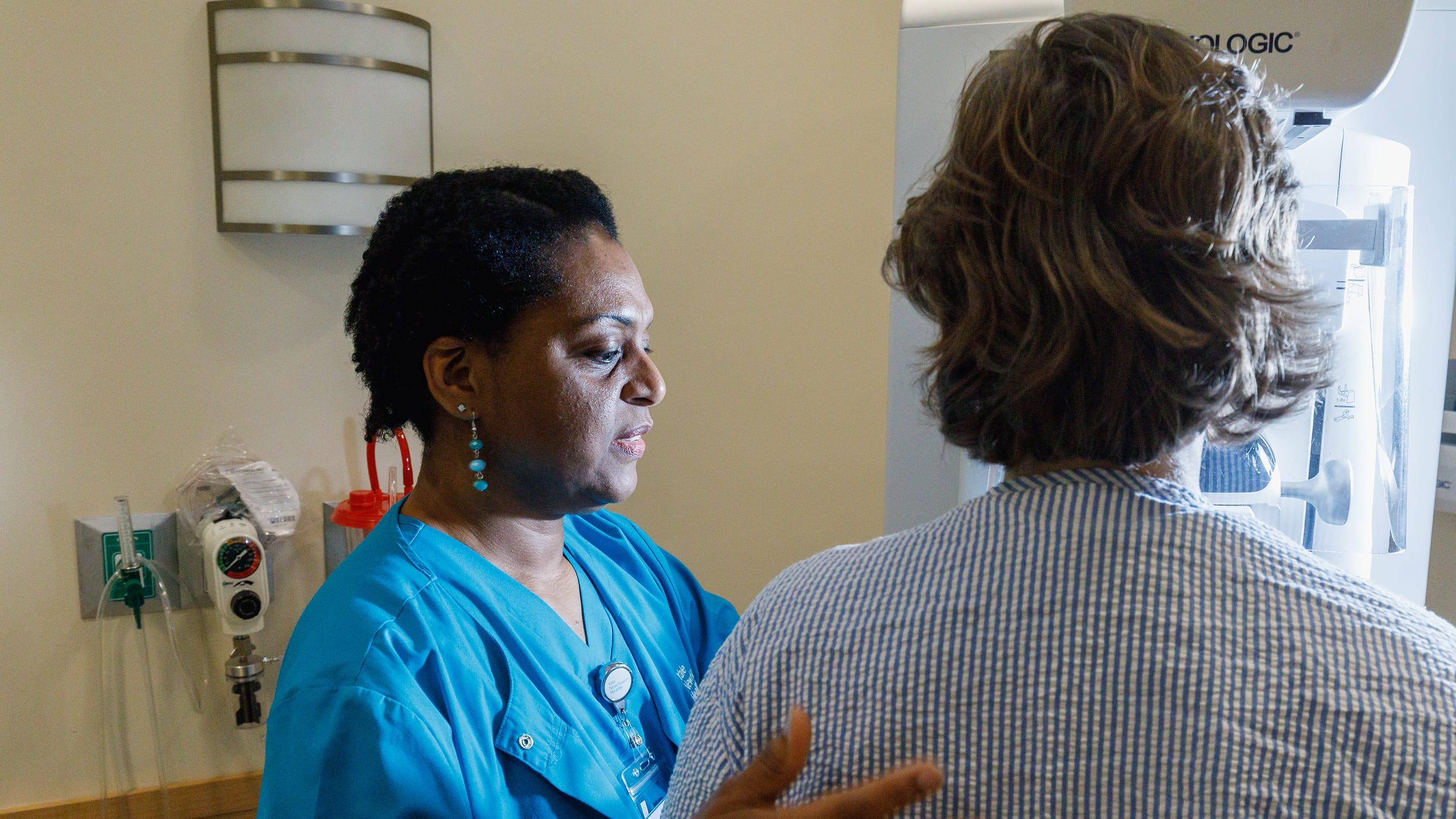 Mammography technician Rhona Hall prepares a fake patient for a 3D mammogram. 