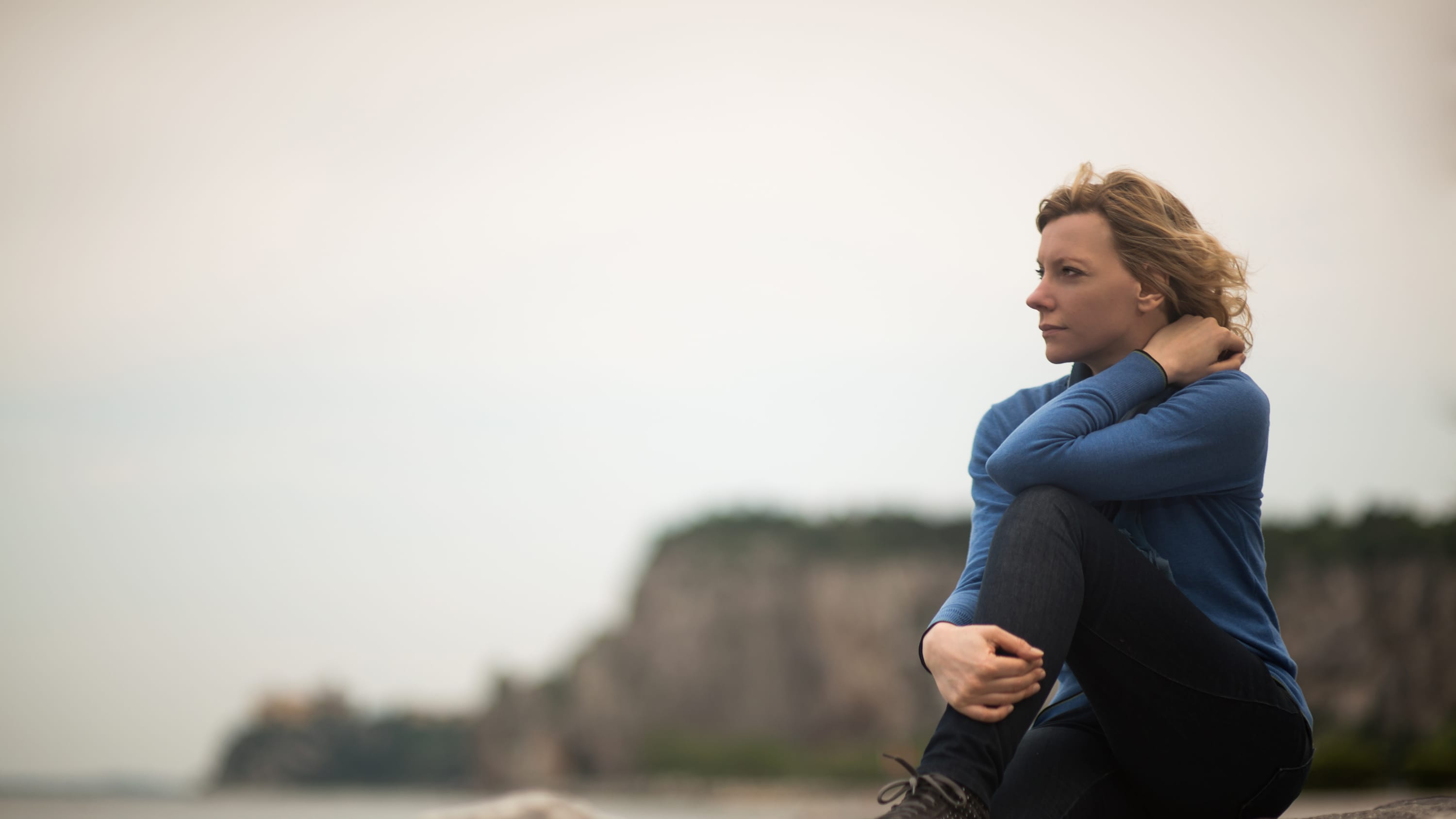 A woman who may need genomic testing for cancer treatment gazes into the distance.