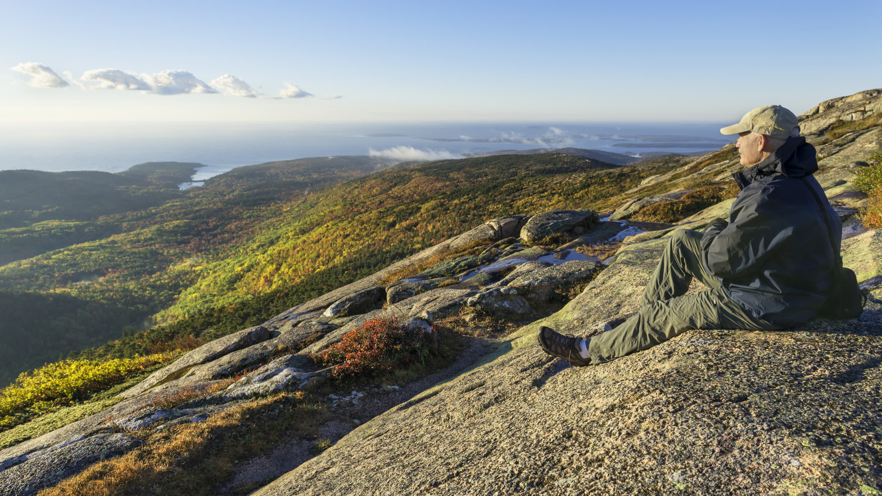A man with colorectal cancer sits on a rock outcropping.
