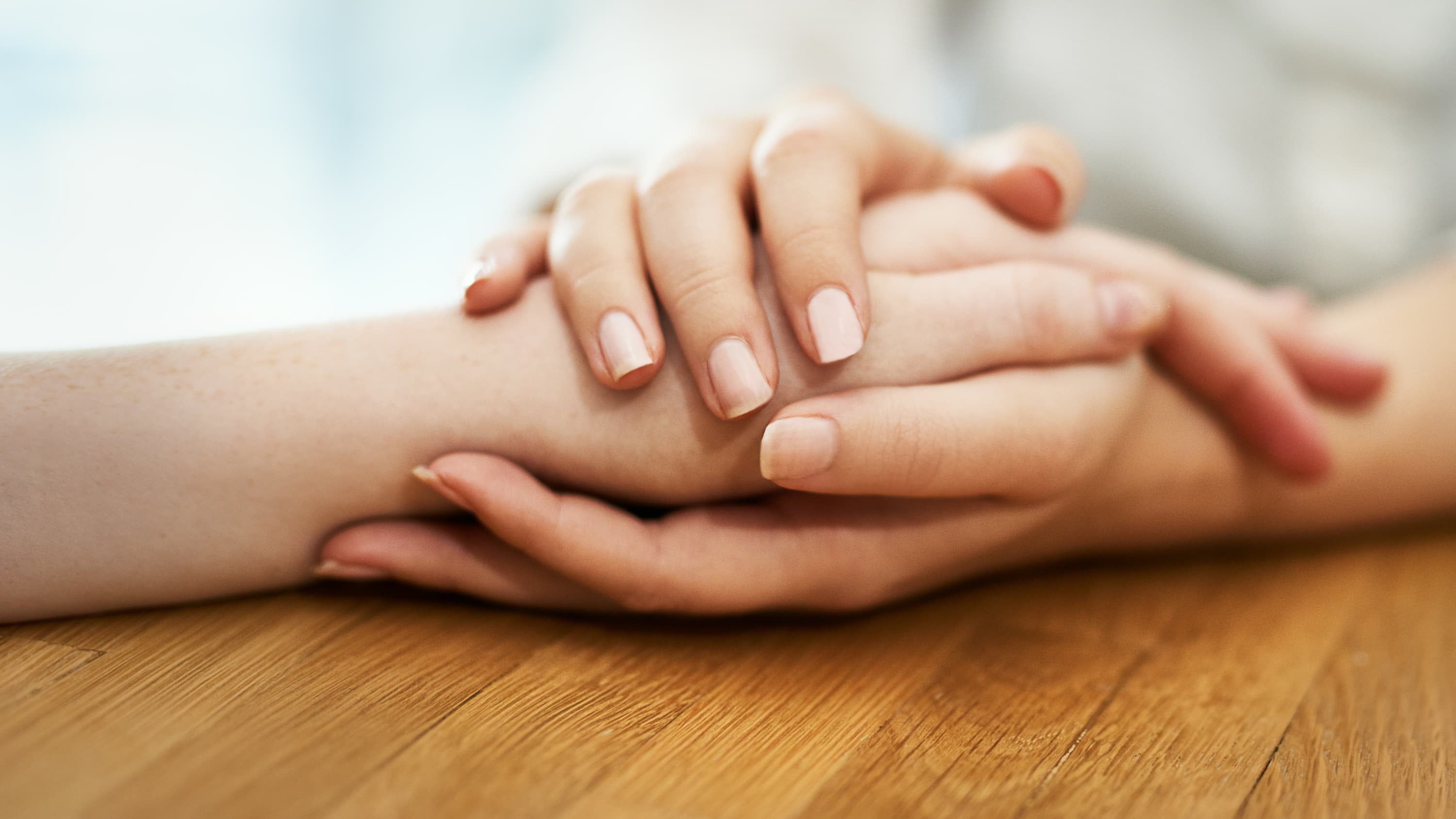A patient is comforted by a family member holding her hand possibly following a skin lymphoma diagnosis.