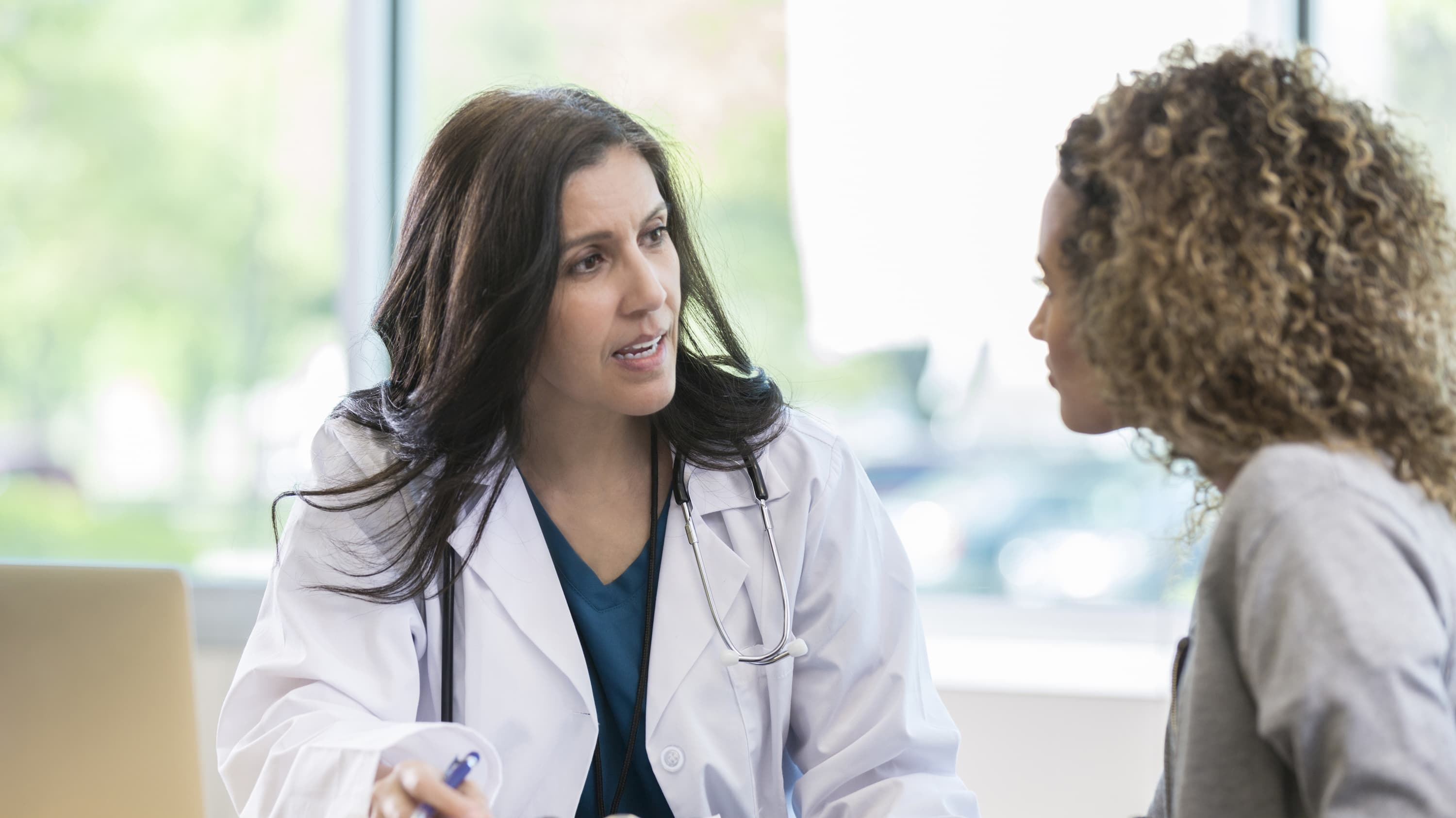 A doctor speaks with her patient, possibly discussing cervical insufficiency