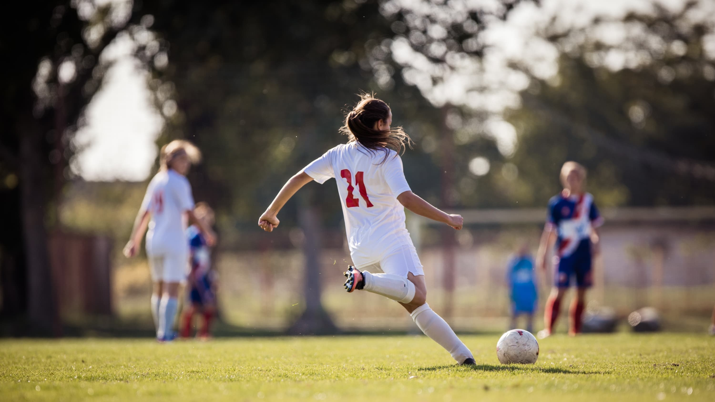 female soccer player kicking a soccer ball