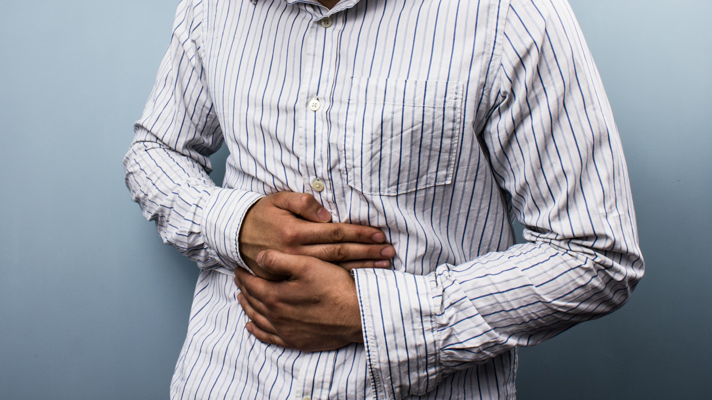 Man holds stomach in discomfort, he is suffering from ulcerative colitis.