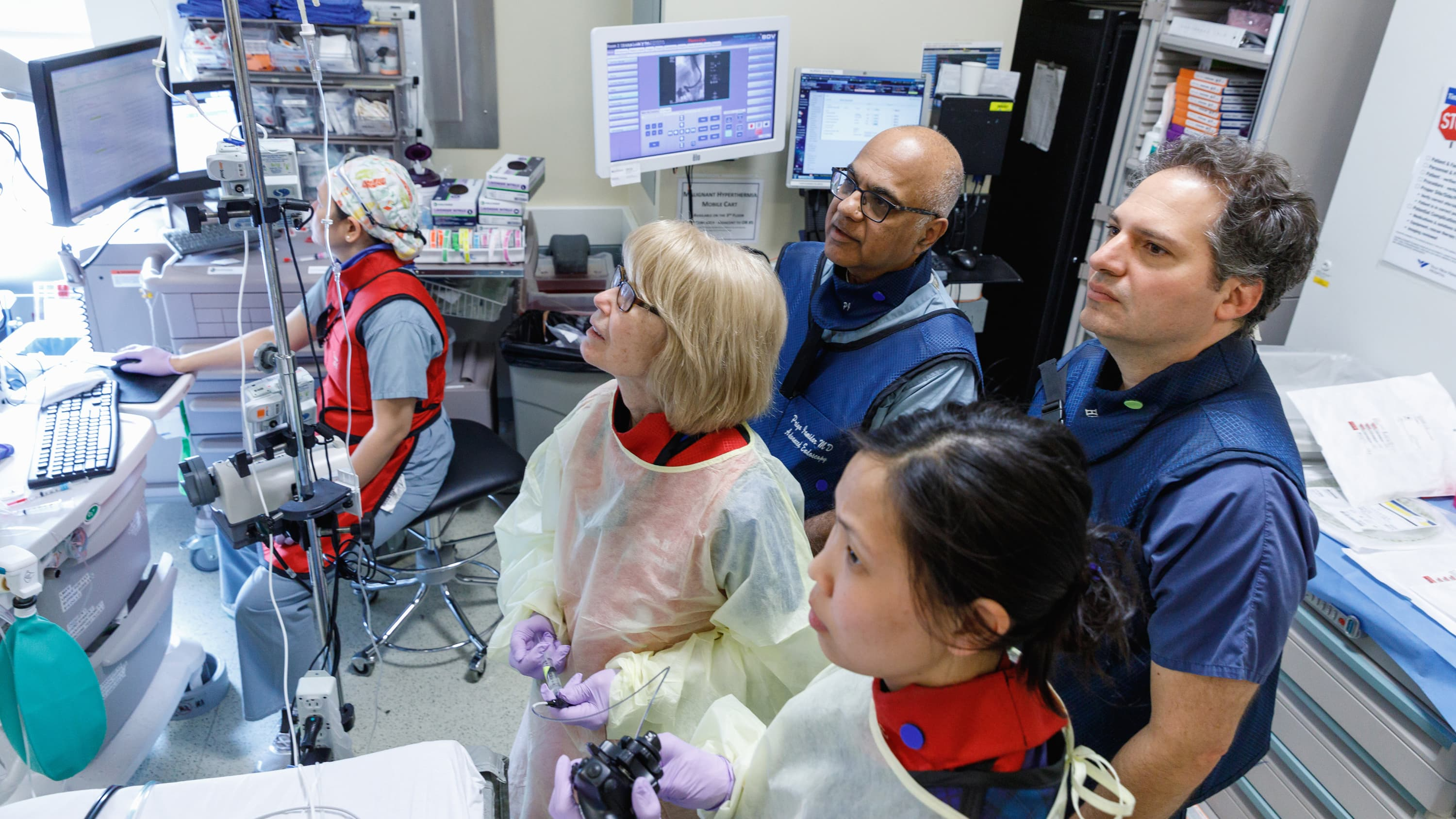 A group of doctor's performing an endoscopic ultrasound look intently in the direction of a screen.