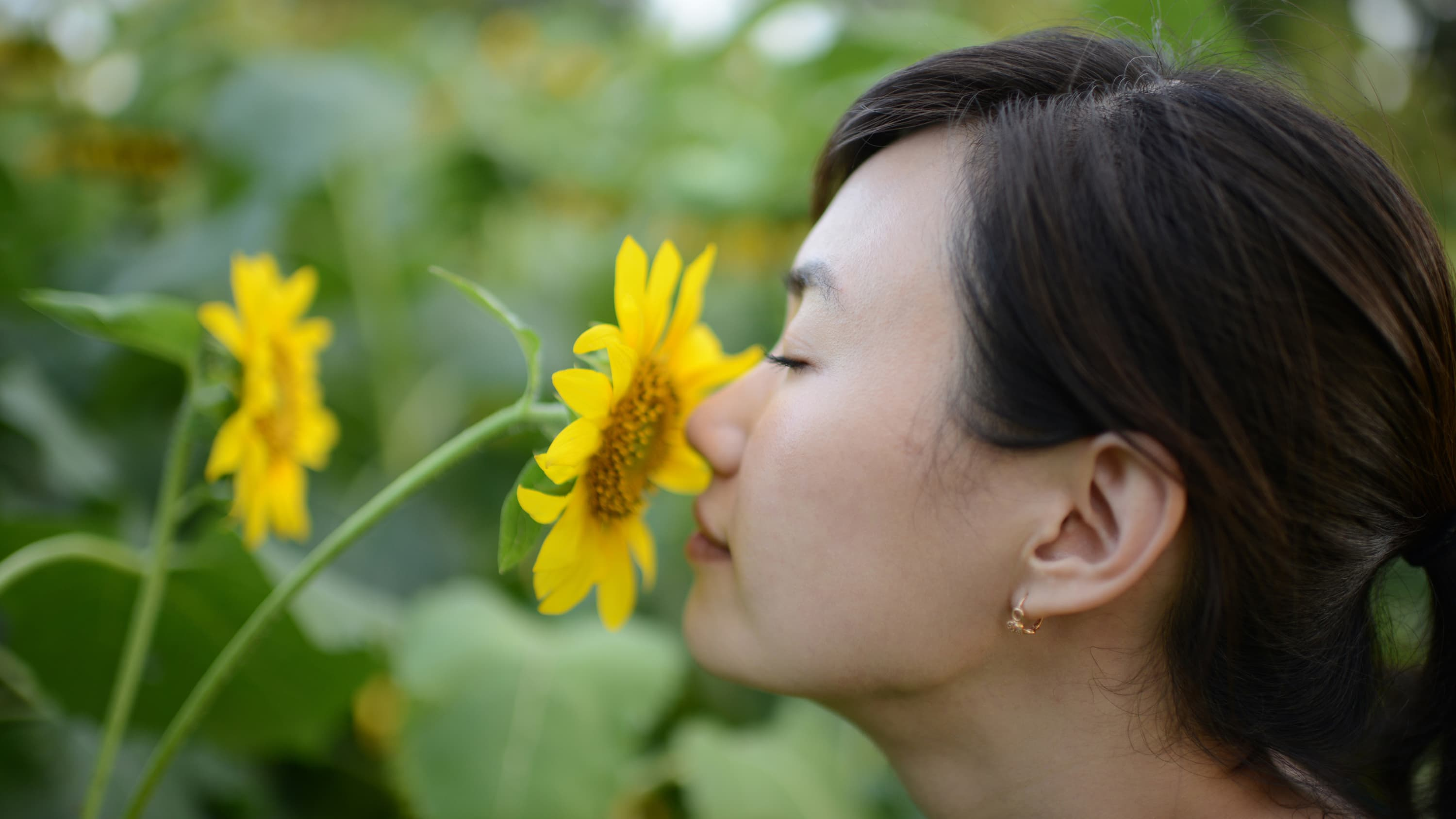 A woman who is trying to (but cannot) smell the flowers because of anosmia.
