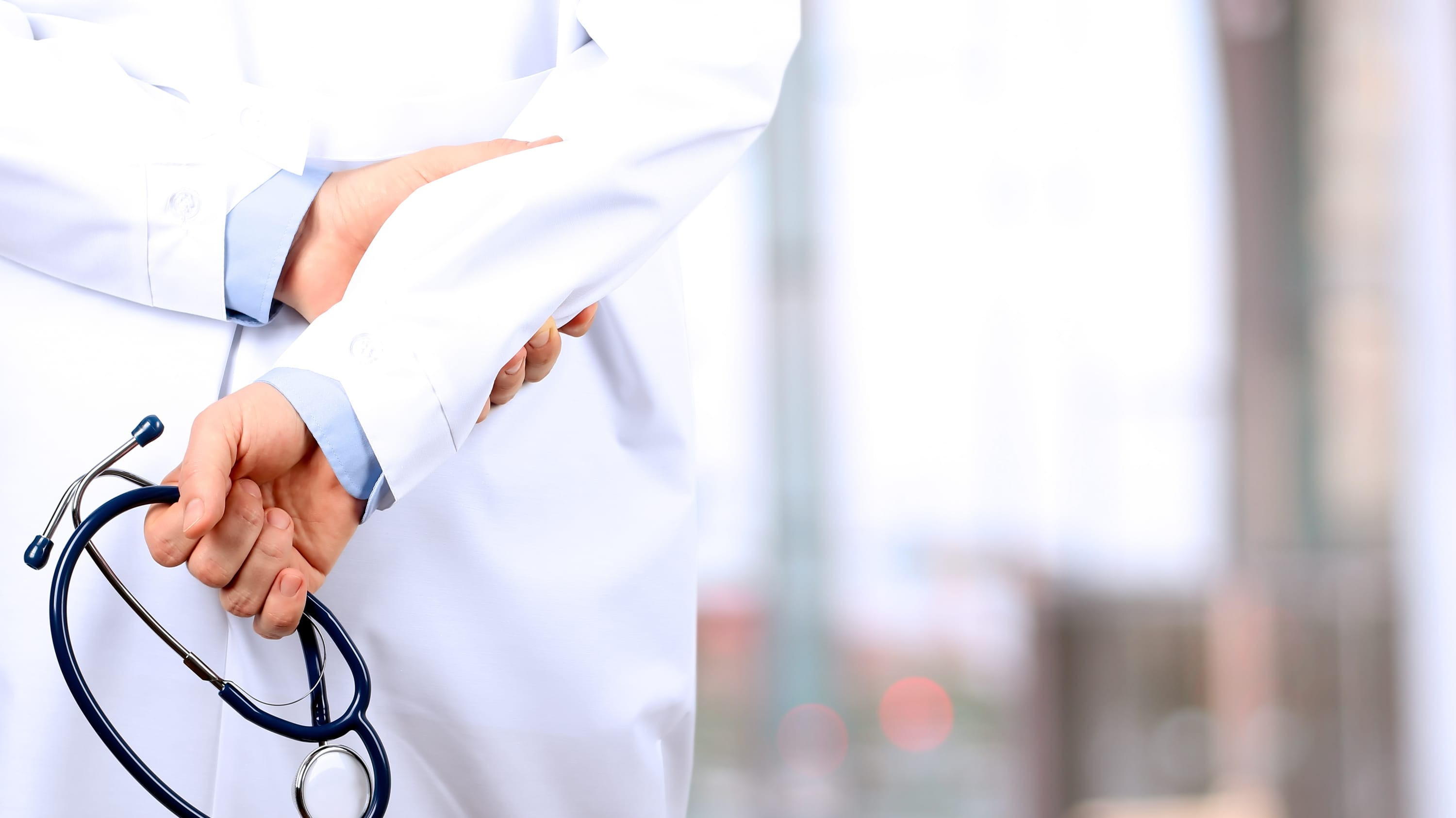 A doctor holds a stethoscope and helps patients with leukemia.