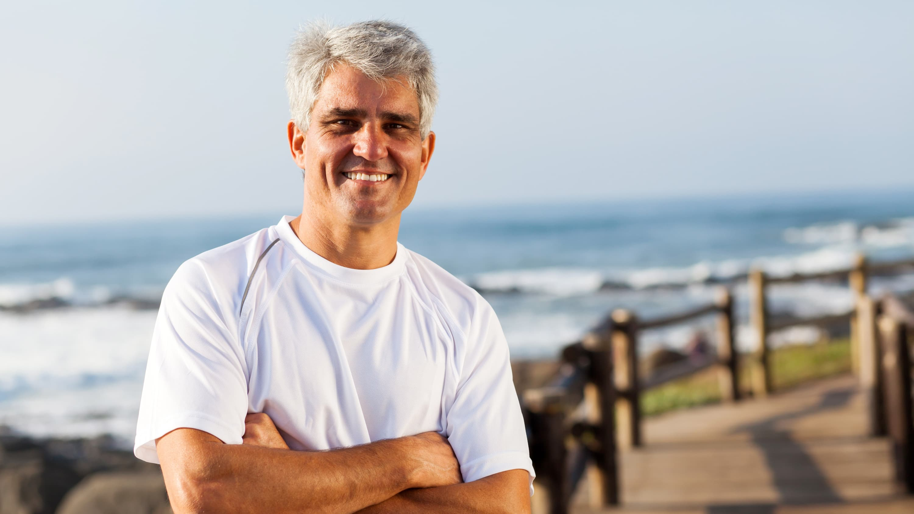 Man with gray hair in a white T-shirt stands on a boardwalk smiling, possibly because of successful cancer surgery