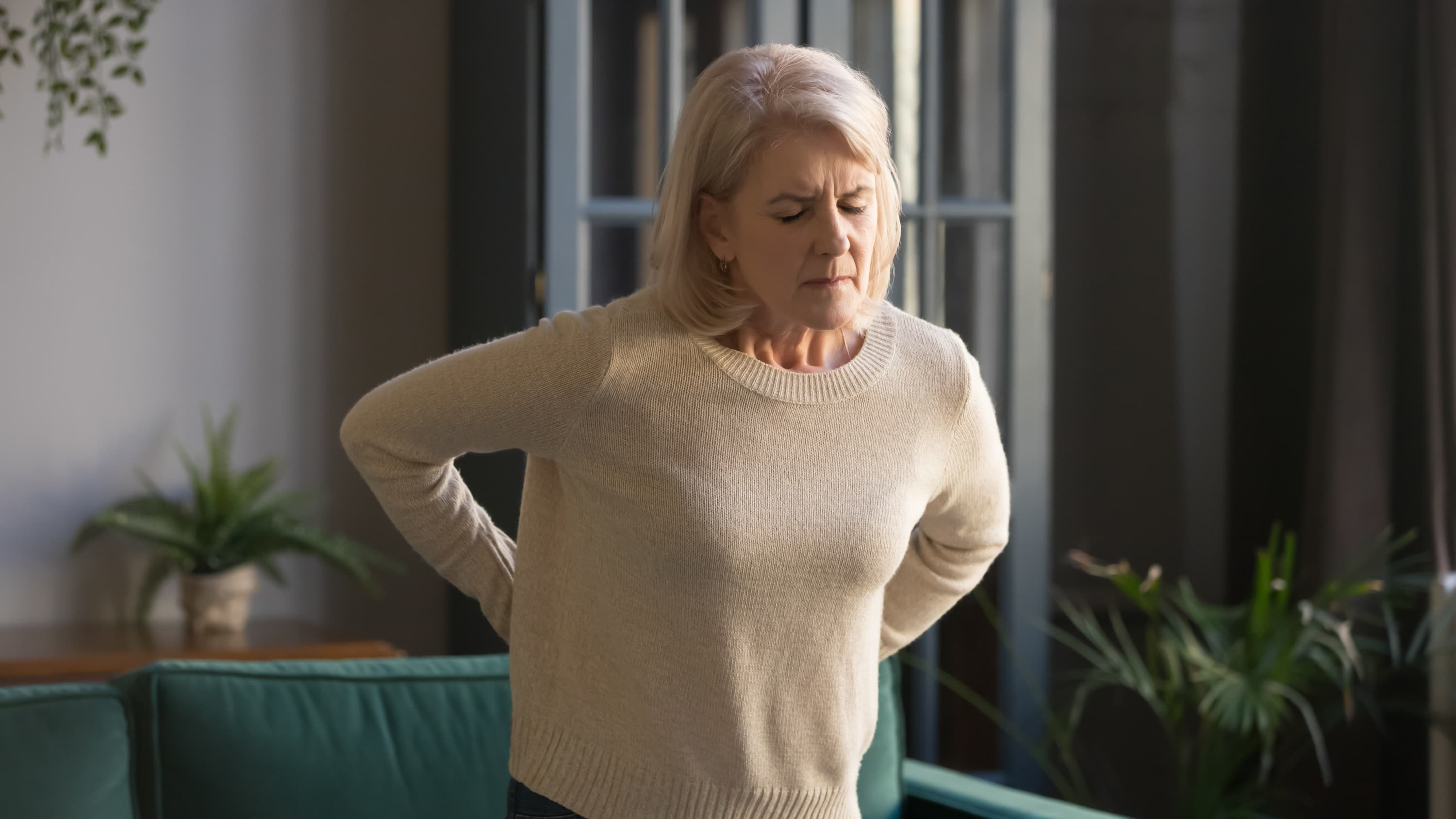 woman suffering from backache, possibly from fibromyalgia
