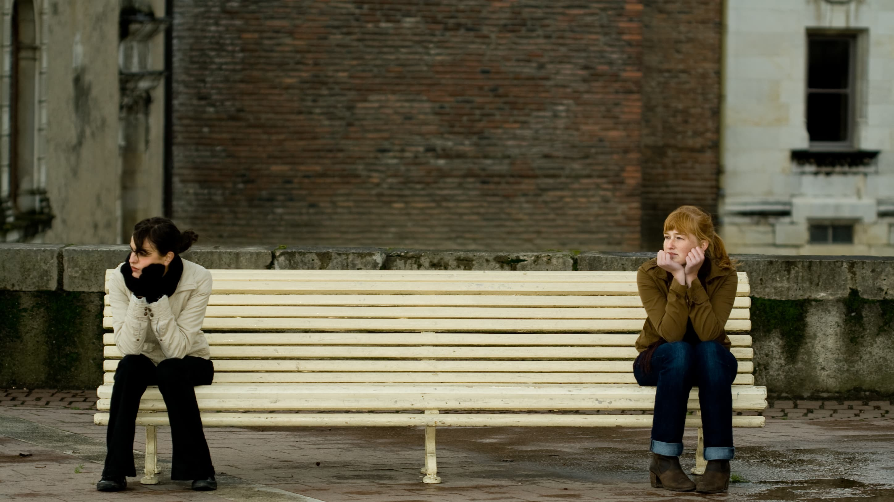 two girls on opposite sides of a bench, practicing social distancing during COVID-19 pandemic