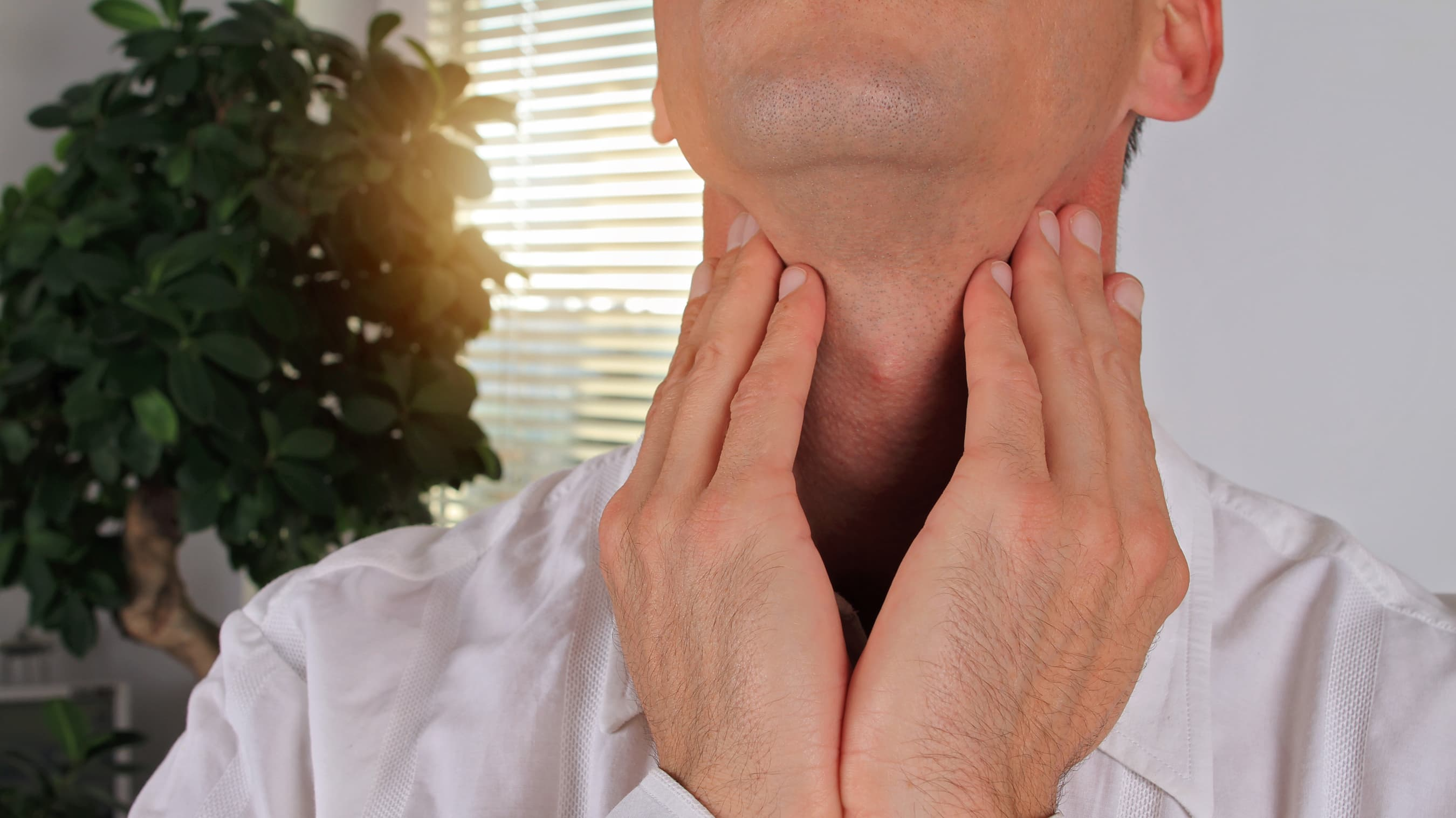 A person who may need radiation therapy for esophageal cancer holds his neck with two hands.