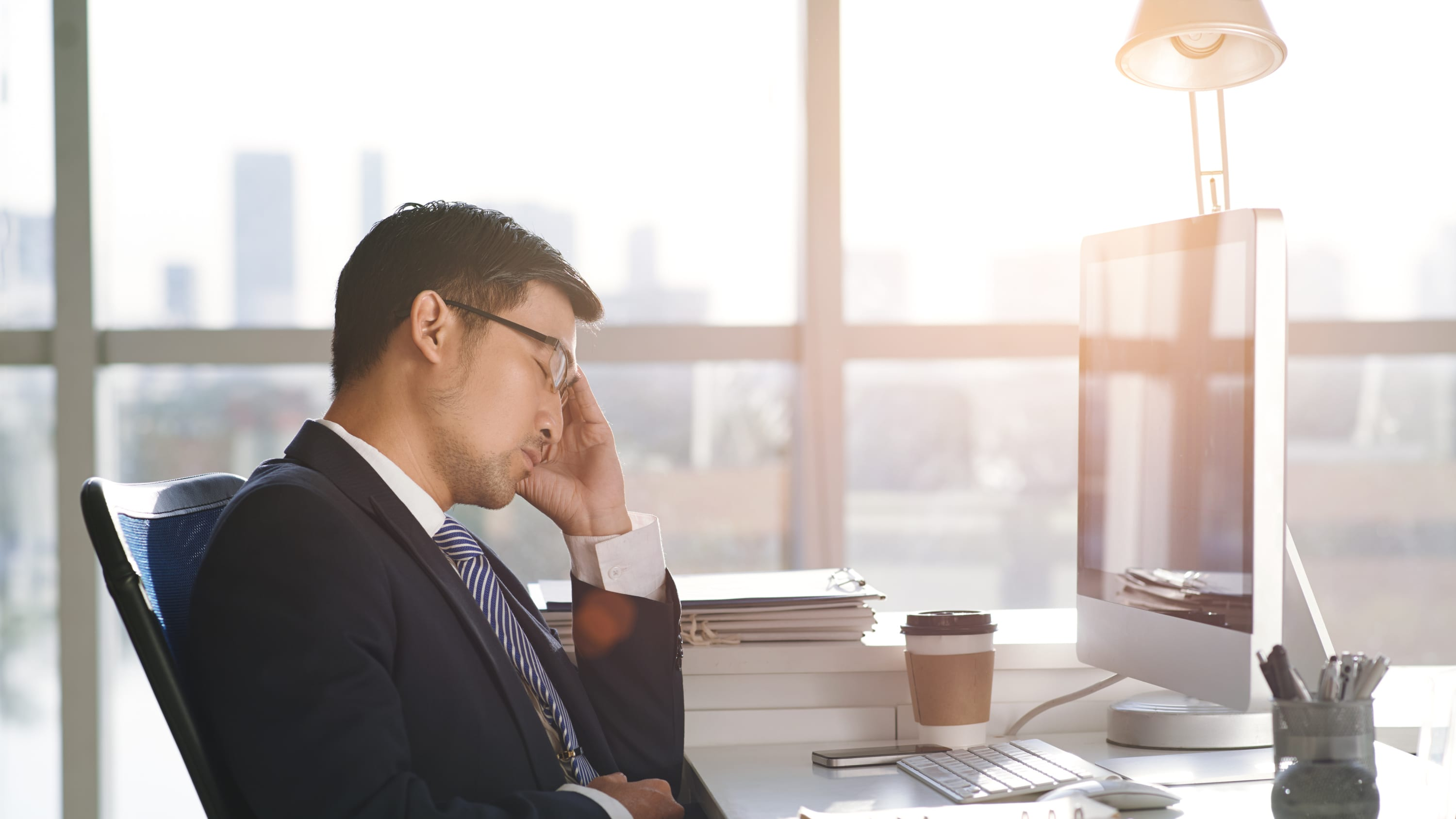 A man in an office who is struggling with insomnia is falling asleep at his desk.